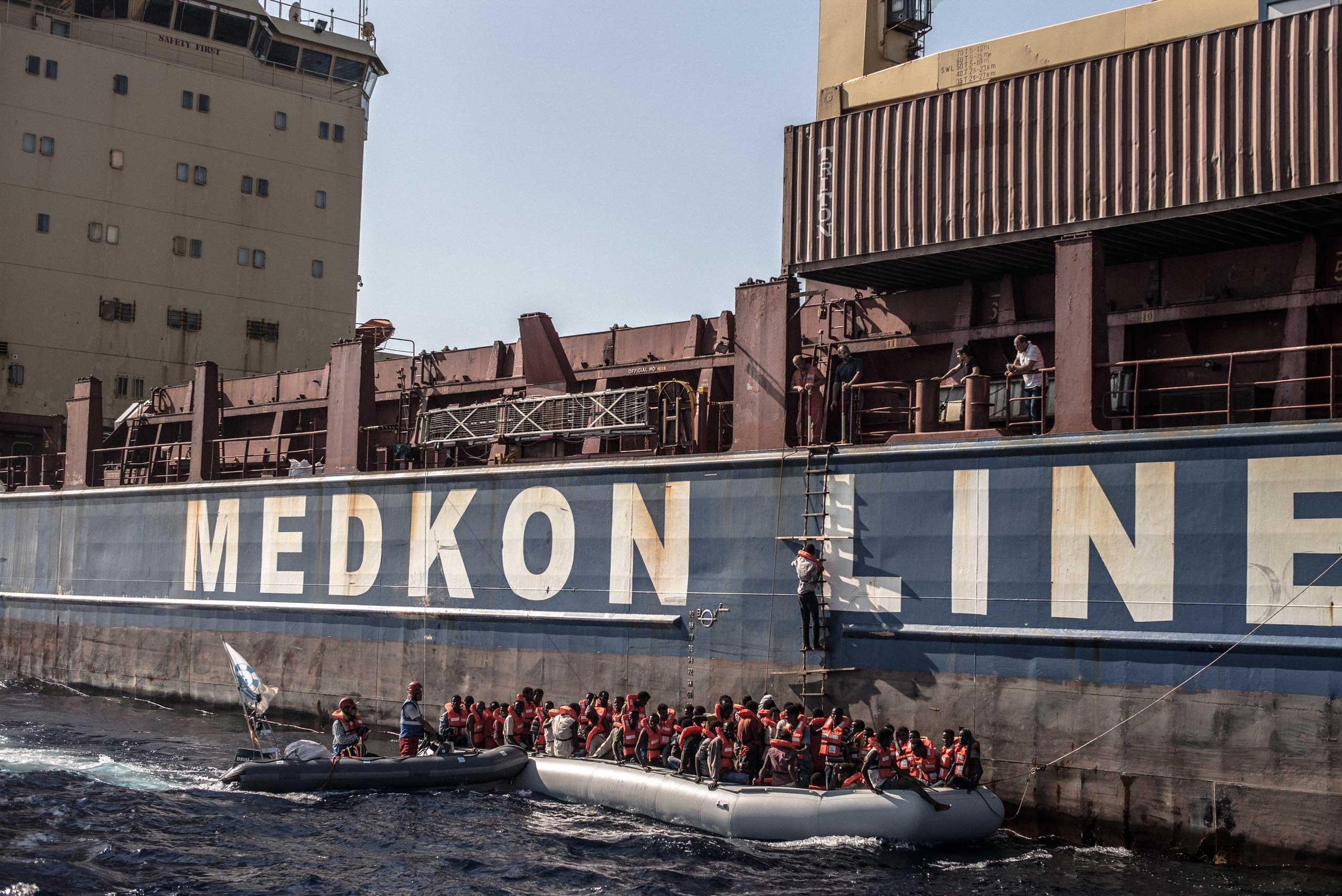 Al Jazeera America: Hands Across WaterThe crew of the Sea-Watch assists migrants boarding the freight ship Shaya, Mediterranean Sea,  on July 23, 2015.