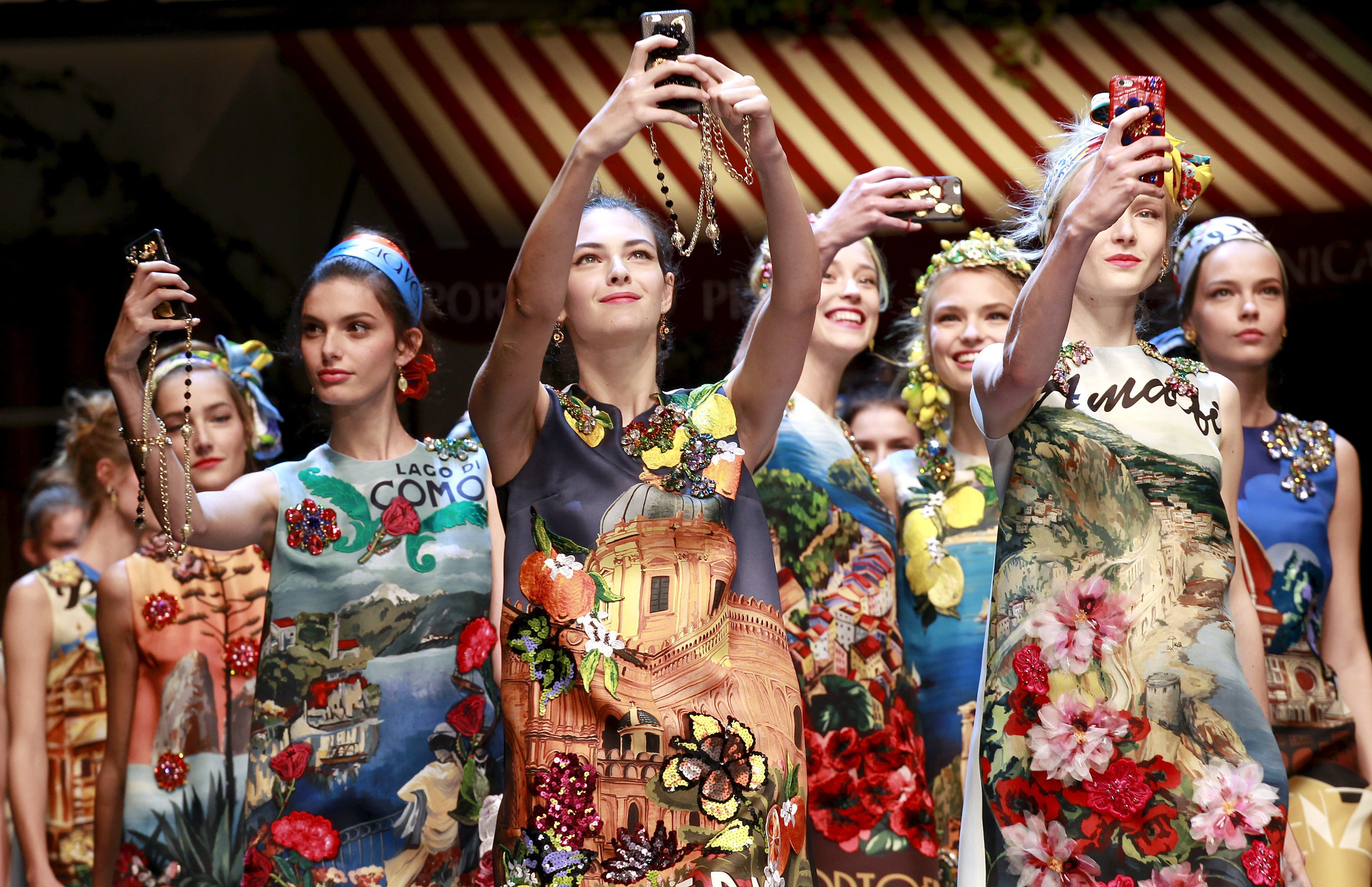 Models take selfie with mobile phones during the parade at the end of the Dolce & Gabbana Spring/Summer 2016 collection during Milan Fashion Week in Italy, on Sept. 27, 2015.