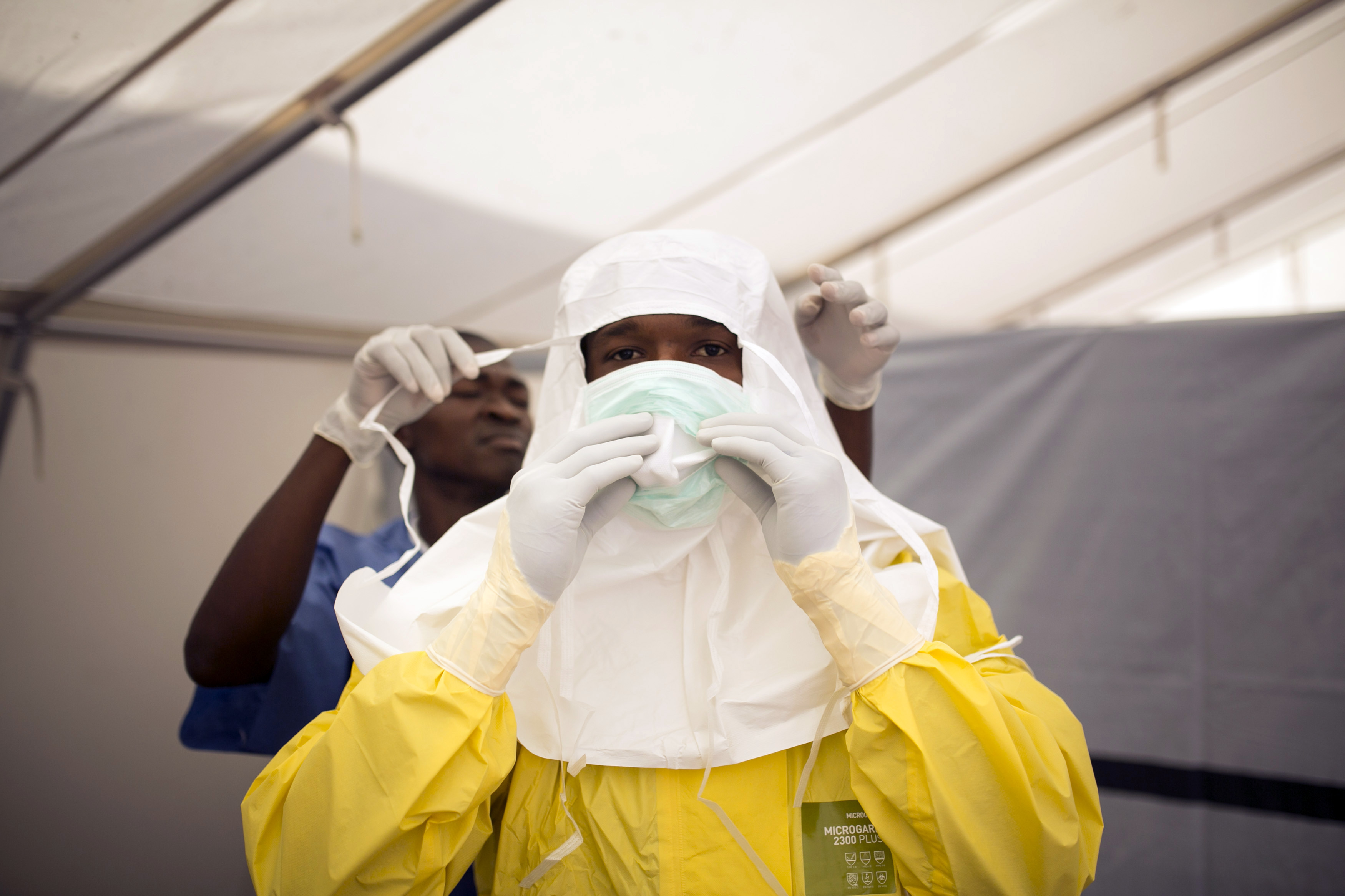 Health workers put on protective gear before entering a quarantine zone at a Red Cross facility in the town of Koidu, Kono district in Eastern Sierra Leone December 19, 2014.