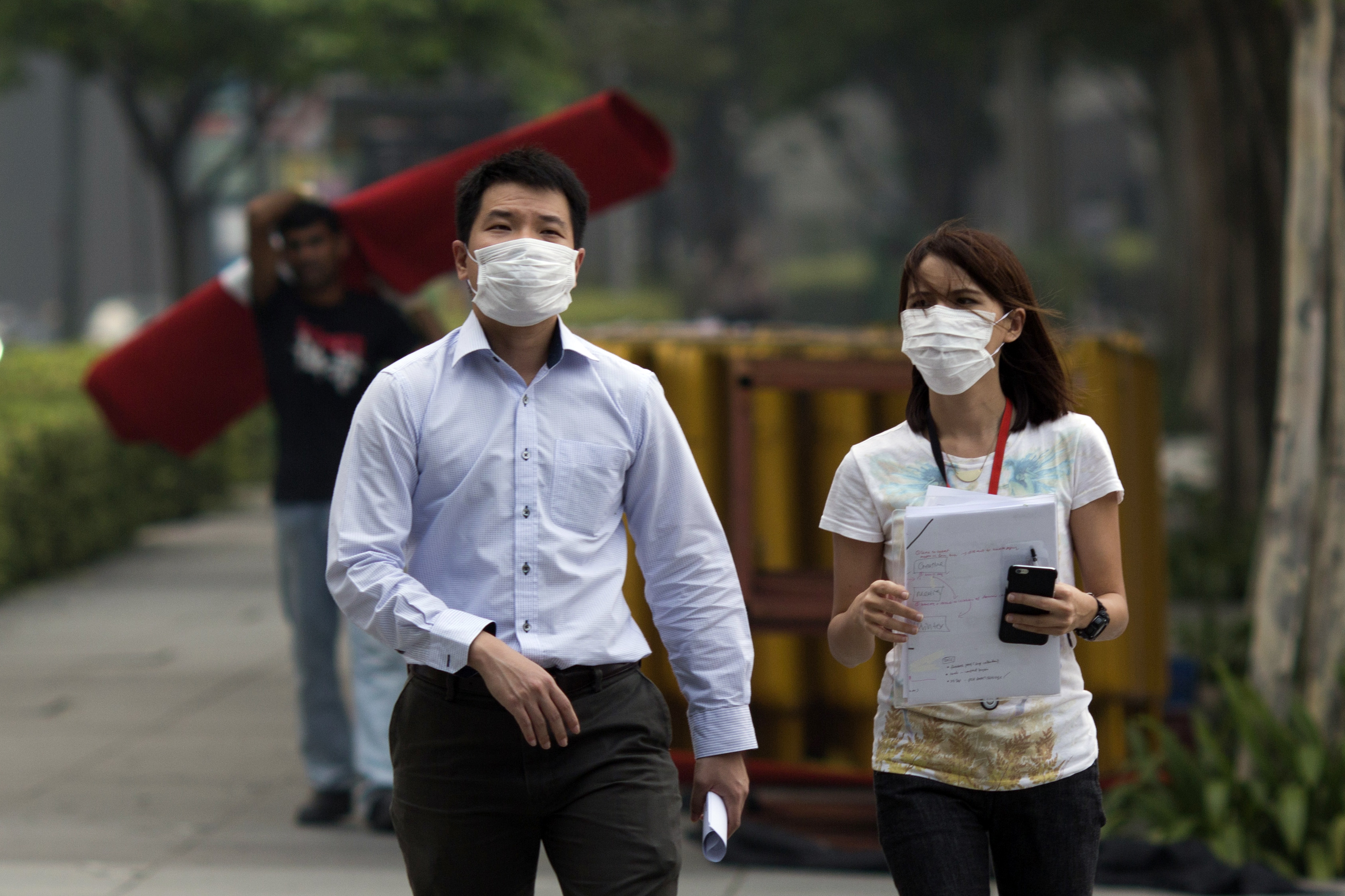 A man and woman wear masks as they work outdoors during a hazy day in Singapore on Sept. 10, 2015