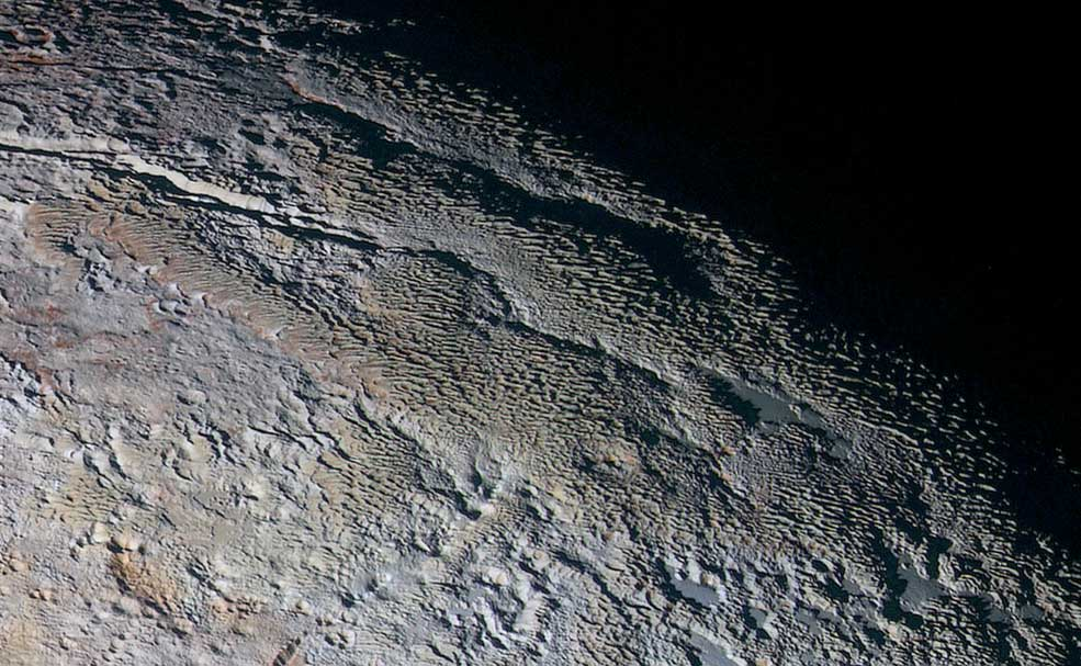 In this extended color image of Pluto taken by NASA's New Horizons spacecraft, rounded and bizarrely textured mountains, informally named the Tartarus Dorsa, rise up along Pluto's day-night terminator and show intricate but puzzling patterns of blue-gray ridges and reddish material in between. This view, roughly 330 miles (530 kilometers) across, combines blue, red and infrared images taken by the Ralph/Multispectral Visual Imaging Camera (MVIC) on July 14, 2015, and resolves details and colors on scales as small as 0.8 miles (1.3 kilometers).
