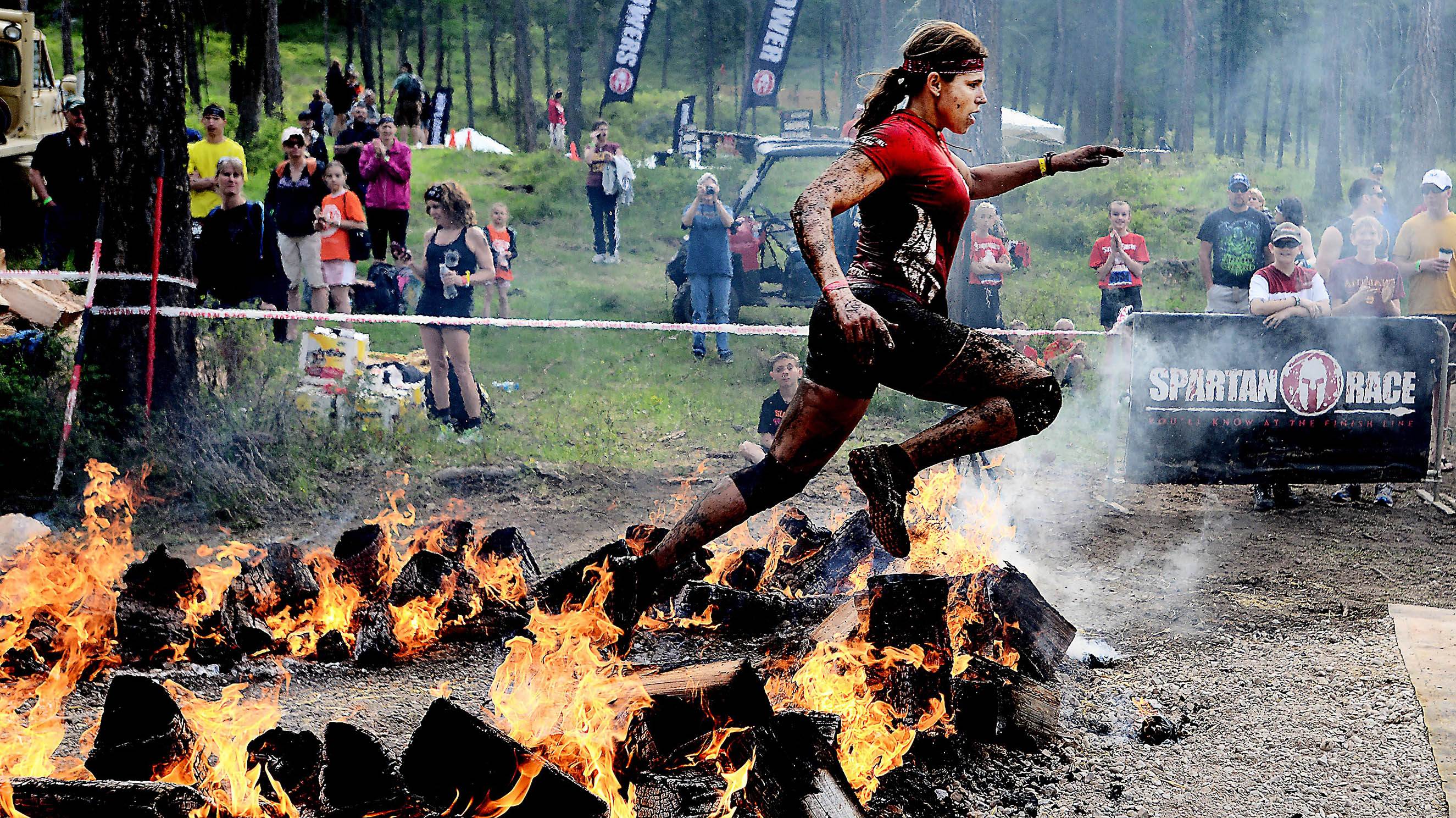 A competitor leaps across a ring of fire during a Spartan Race in Montana. The events are now in 20 countries, and the championship will air on NBC