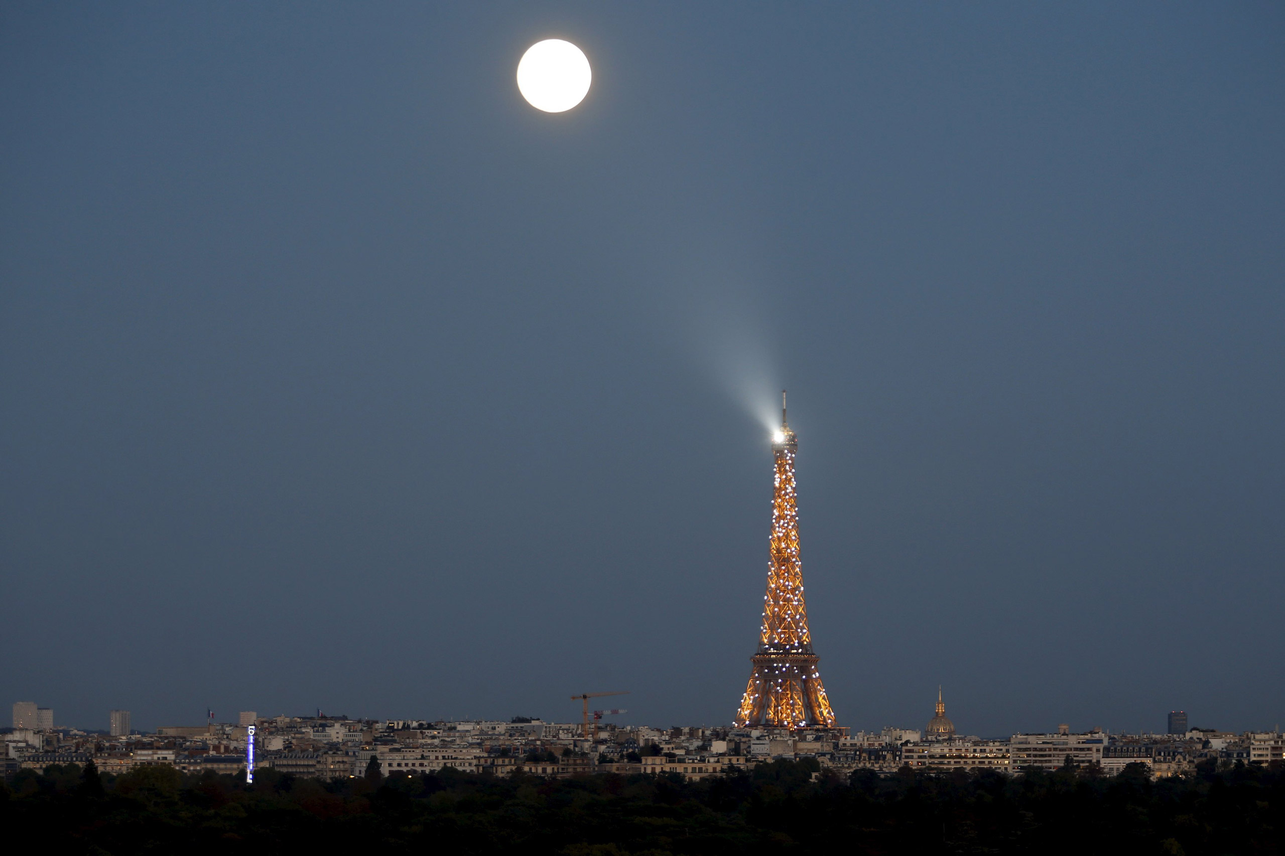 A super moon rises in the sky near the Eiffel tower in Paris on Sept. 27, 2015.