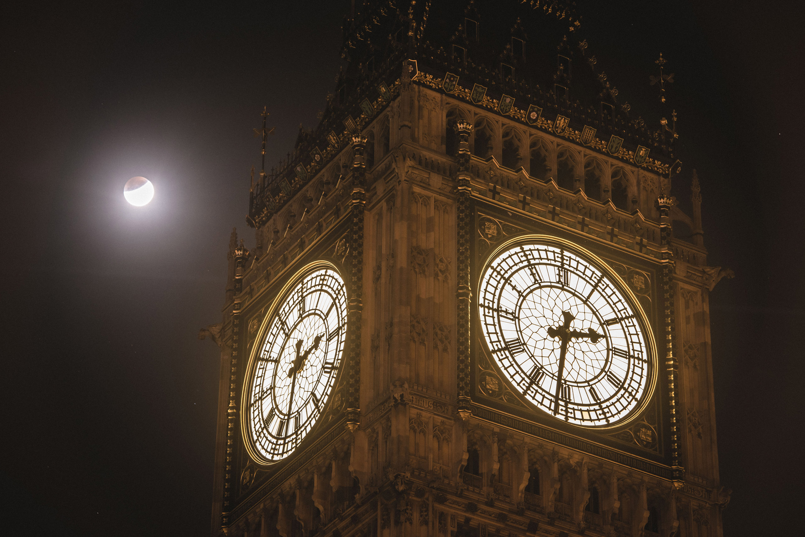 The Supermoon is seen during the early stages of the Lunar Eclipse near Big Ben on Sept. 28, 2015 in London.