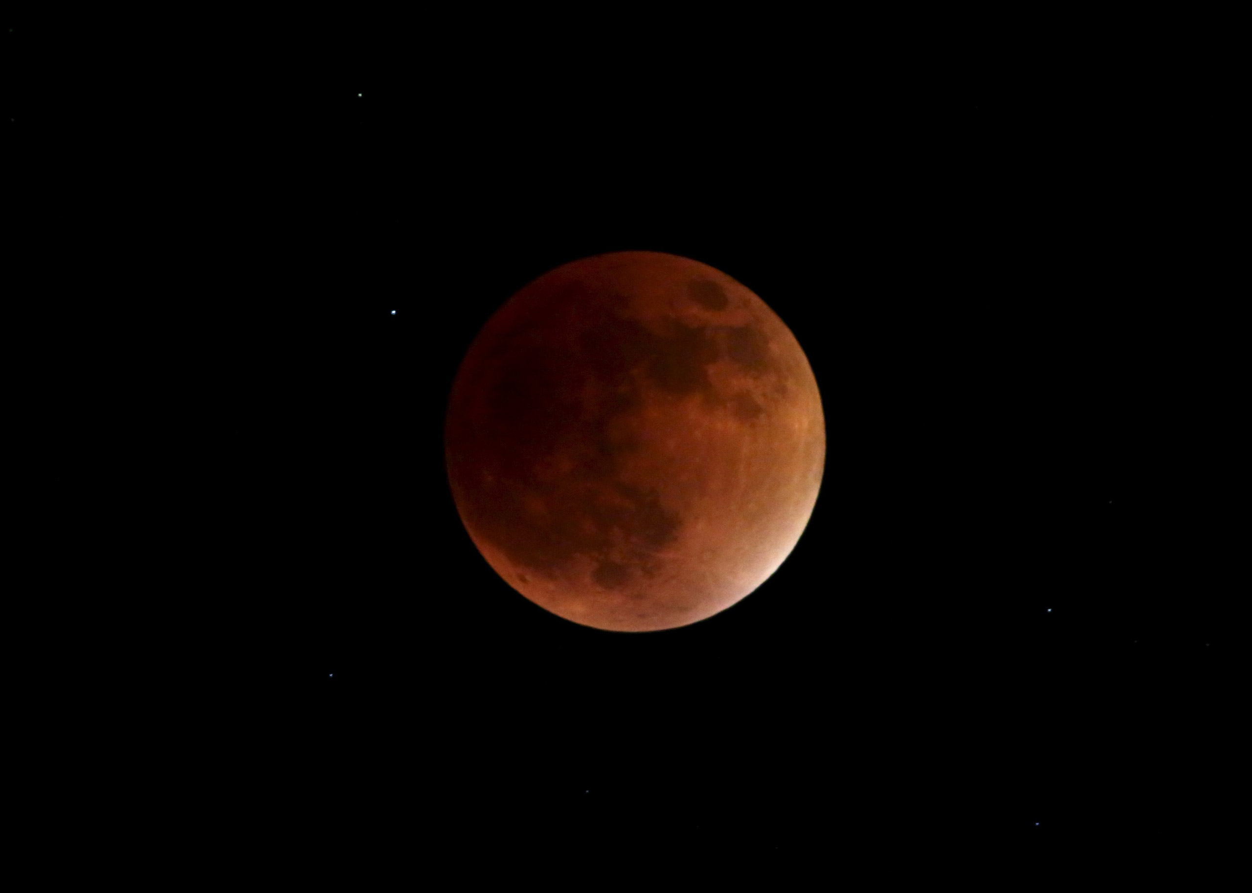 The supermoon appears red during the total lunar eclipse in the sky over Port-of-Spain on Sept. 27, 2015.