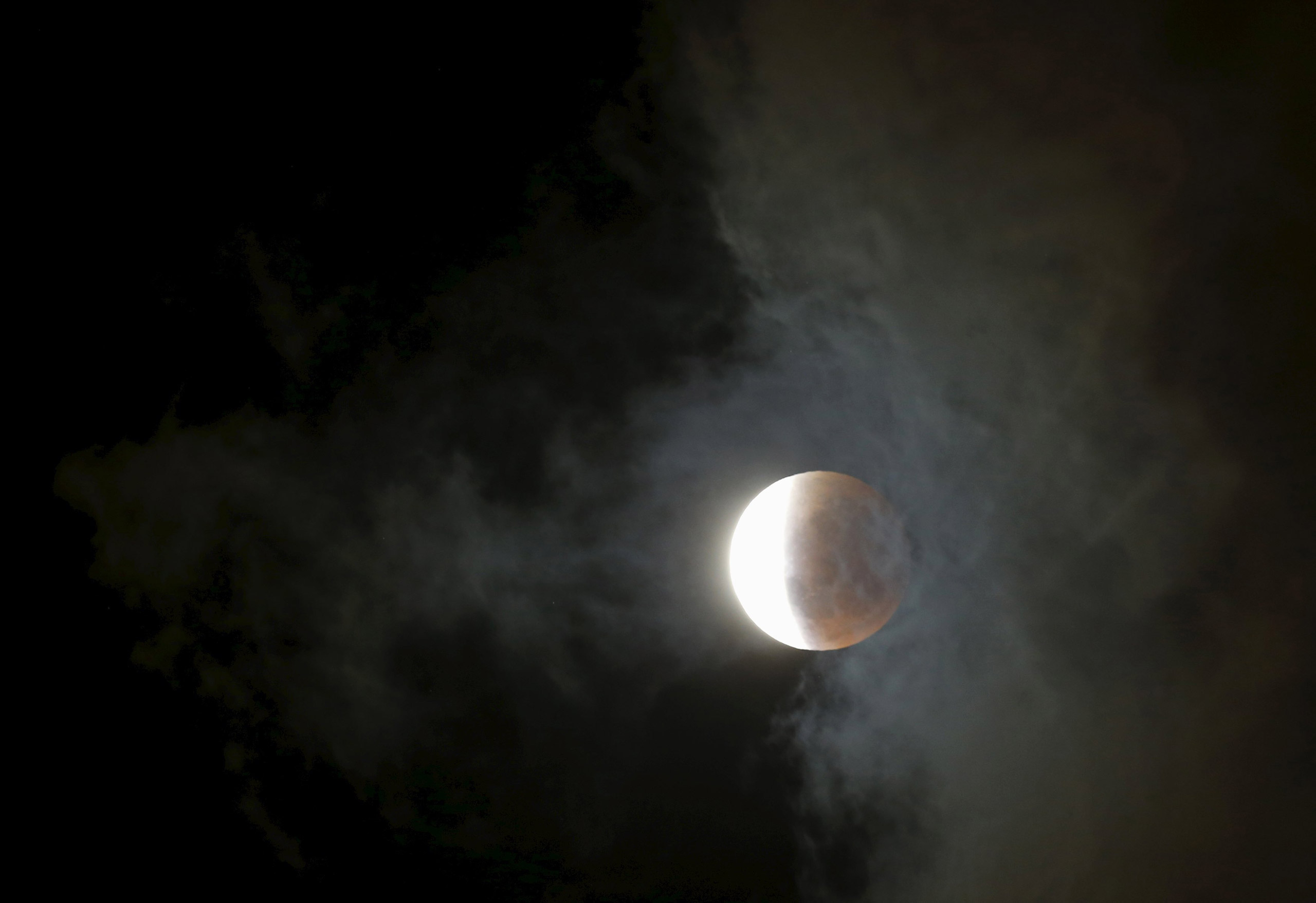 Clouds pass over the Supermoon as it is partially eclipsed over Cape Town on Sept. 28, 2015.