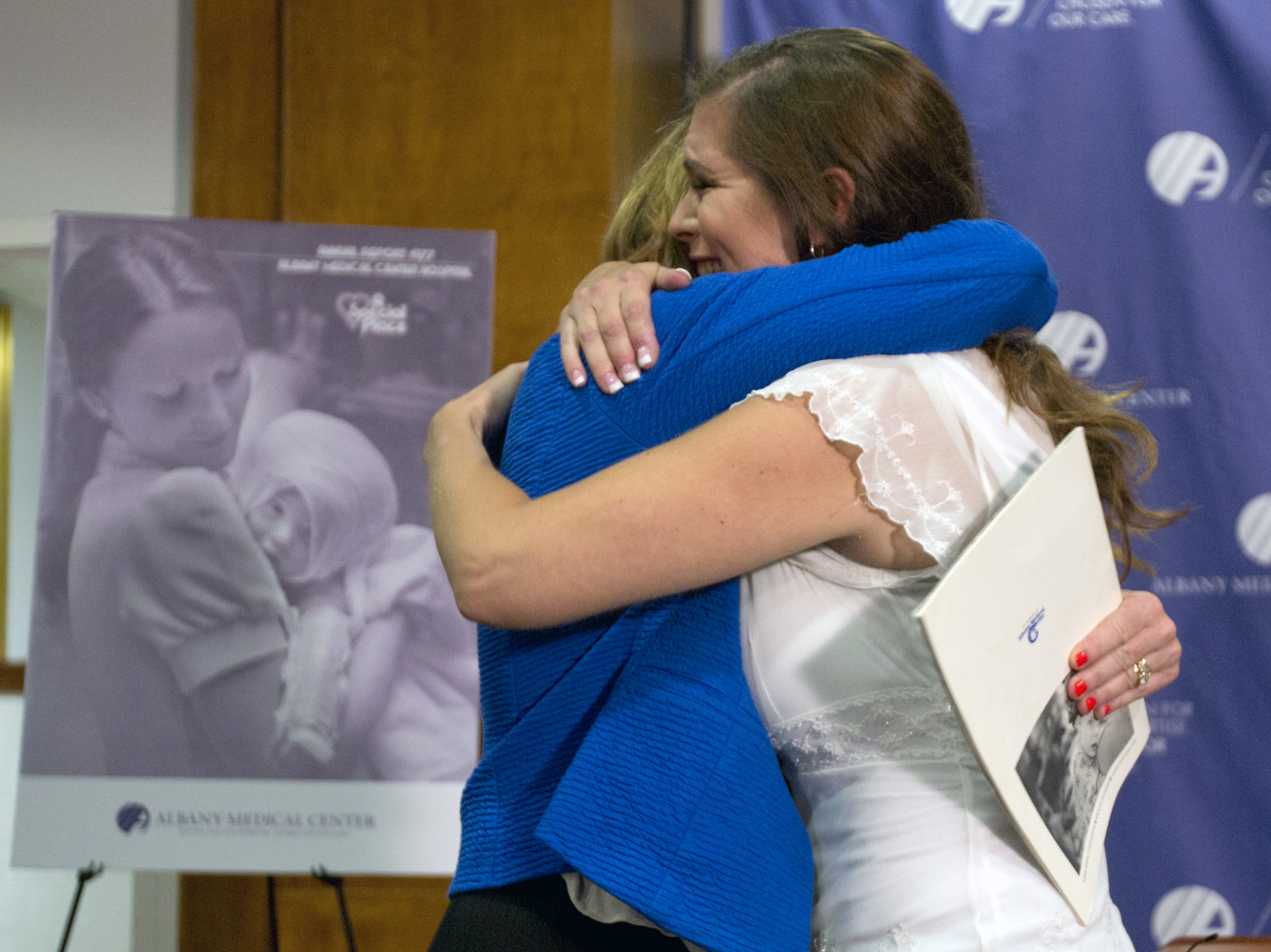 Nurse Susan Berger (L) and Amanda Scarpinati hug during a news conference at Albany Medical Center in Albany, N.Y. on Sept. 29, 2015.