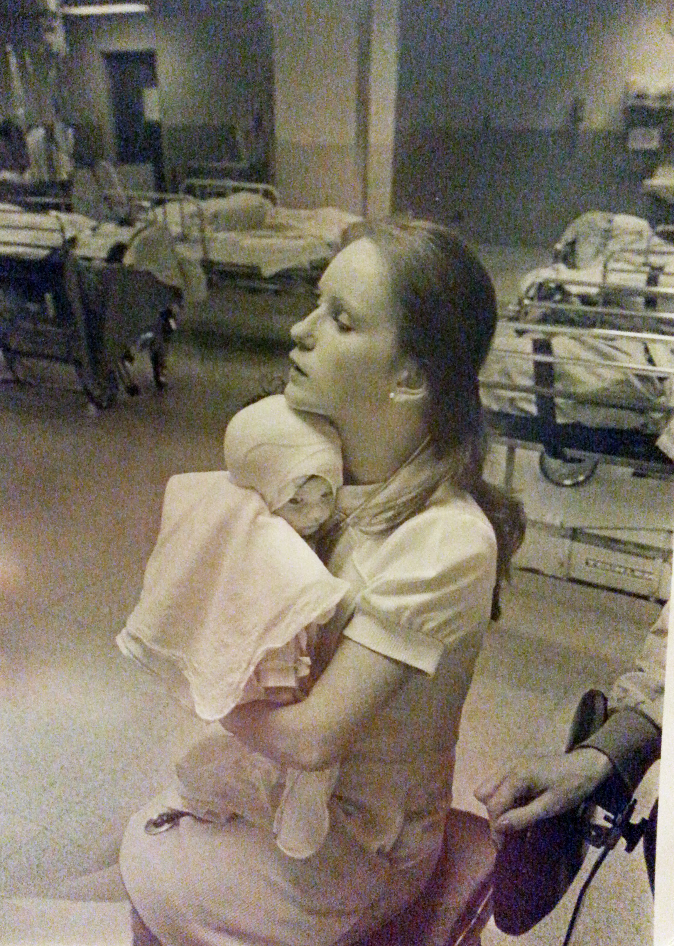 In this 1977 photo provided by Albany Medical Center, nurse Susan Berger cuddles infant Amanda Scarpinati, who had been severely burned by a steam vaporizer at home, in the pediatric unit at Albany Medical Center in Albany, N.Y.