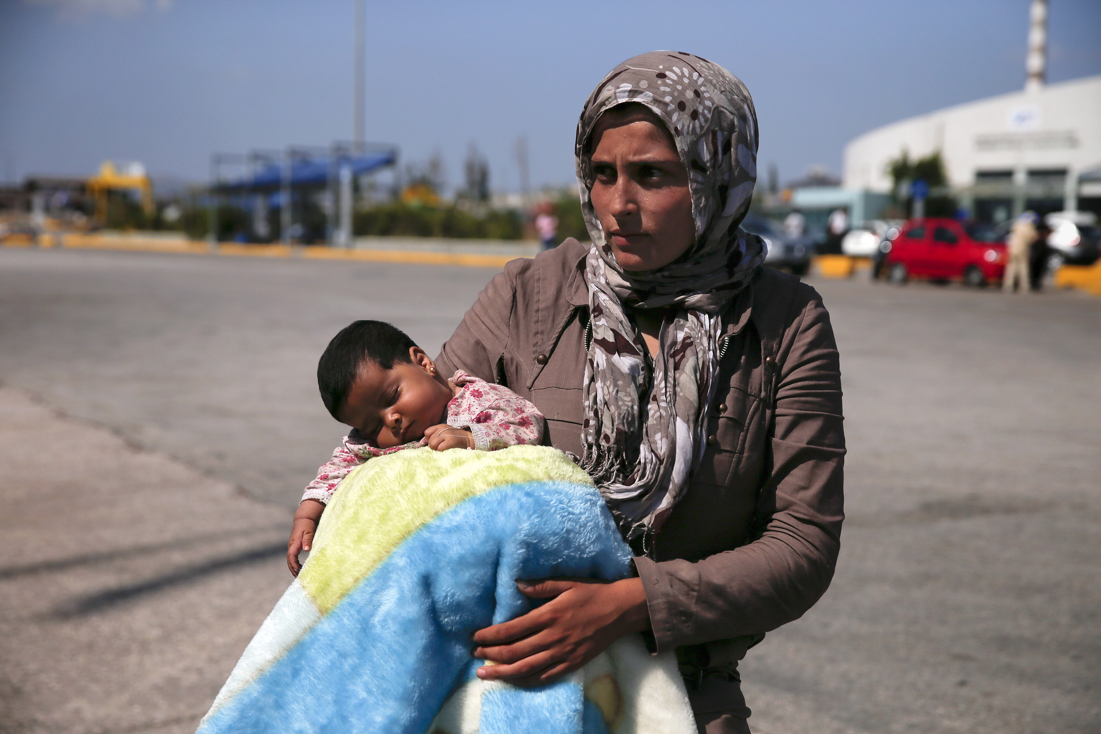 A Syrian refugee holds her baby following their arrival onboard the Eleftherios Venizelos passenger ship at the port of Piraeus, near Athens, Greece on Sept. 8, 2015.