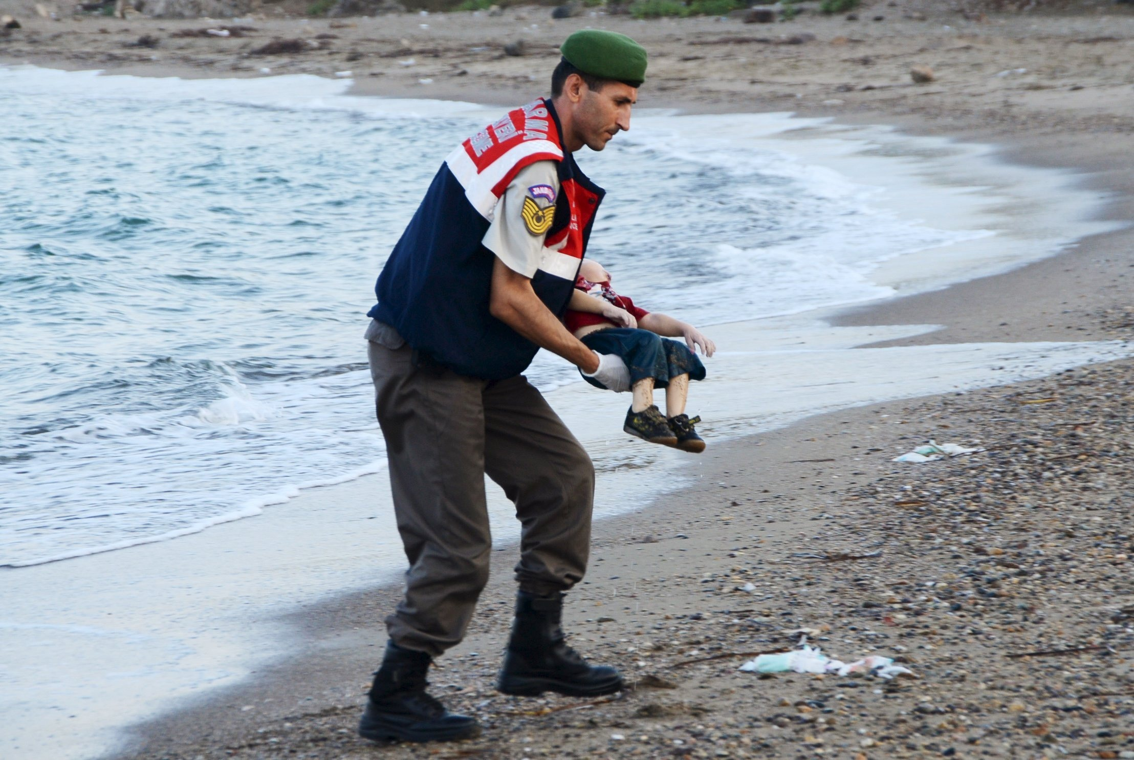 A Turkish gendarme carries the body of Alan Kurdi, 3, who drowned along with his brother Galip, 5, and their mother, in a failed attempt to sail to the Greek island of Kos, in the coastal town of Bodrum, Turkey, on Sept. 2, 2015.