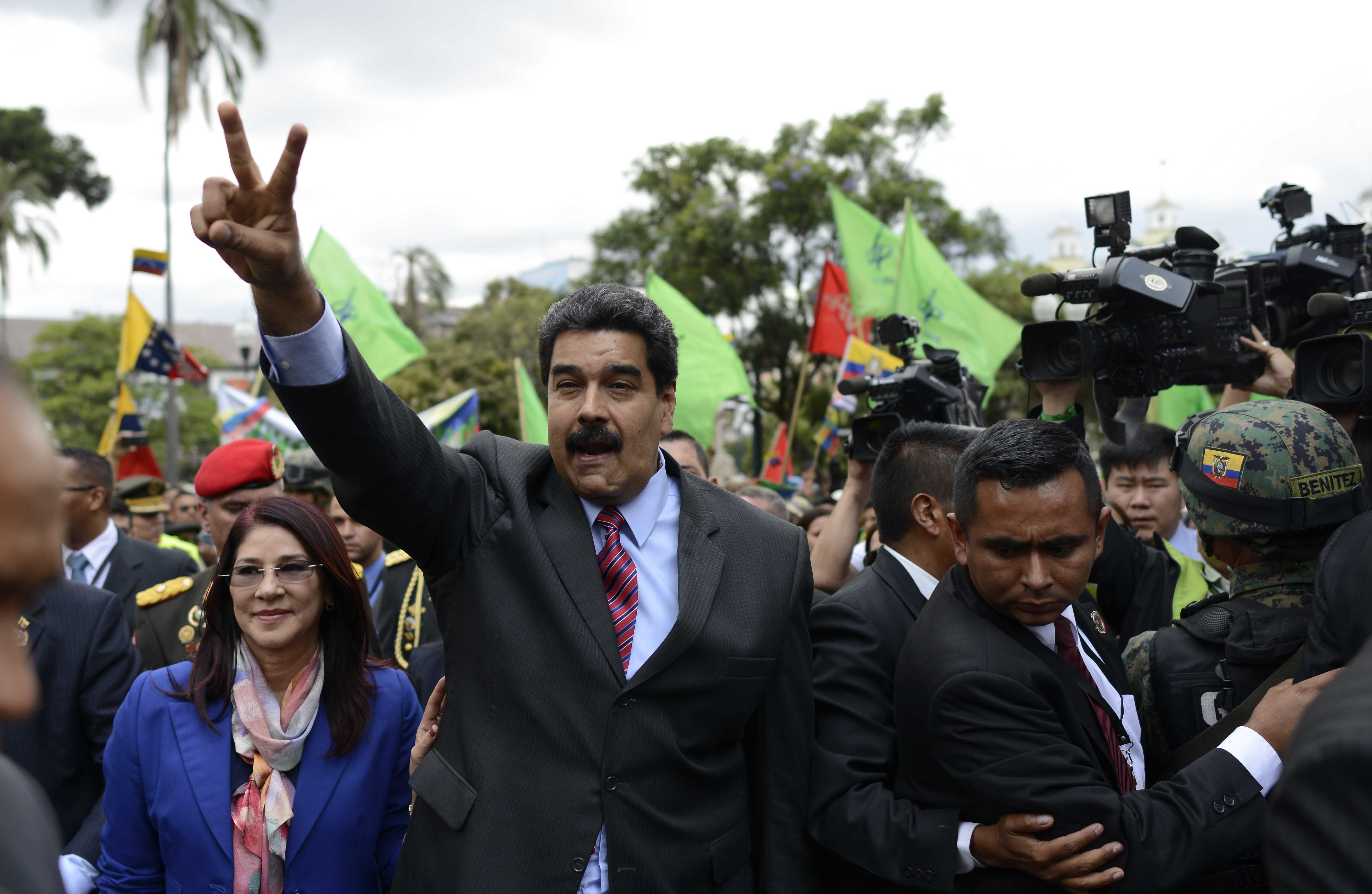 Venezuela's President Nicolas Maduro, accompanied by his first lady Cilia Flores, flashes a peace sign as he arrives at government palace, in Quito, Ecuador, Sept. 21, 2015.
