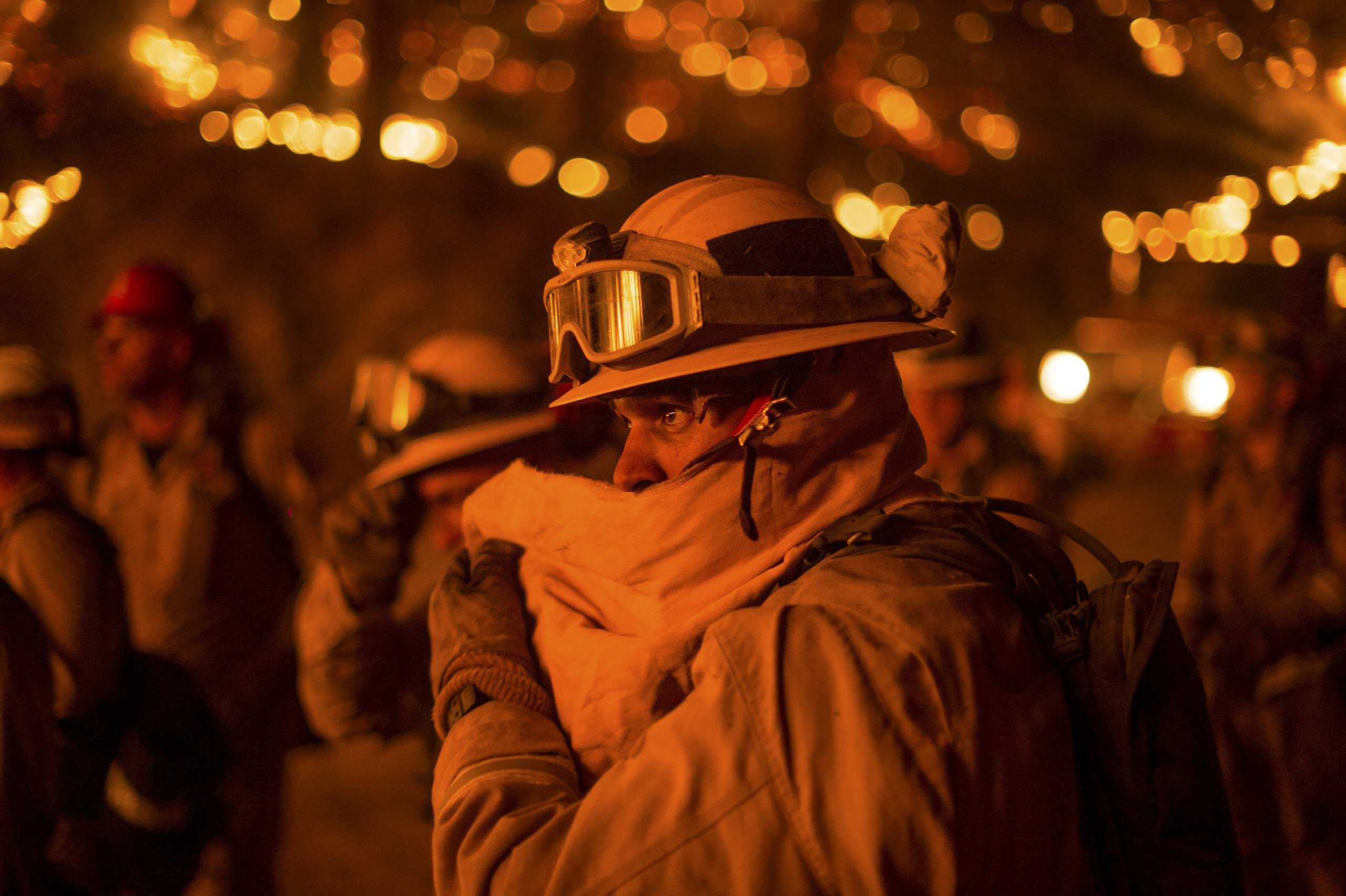 A firefighter covers his face while battling the Butte fire near San Andreas, California September 12, 2015.