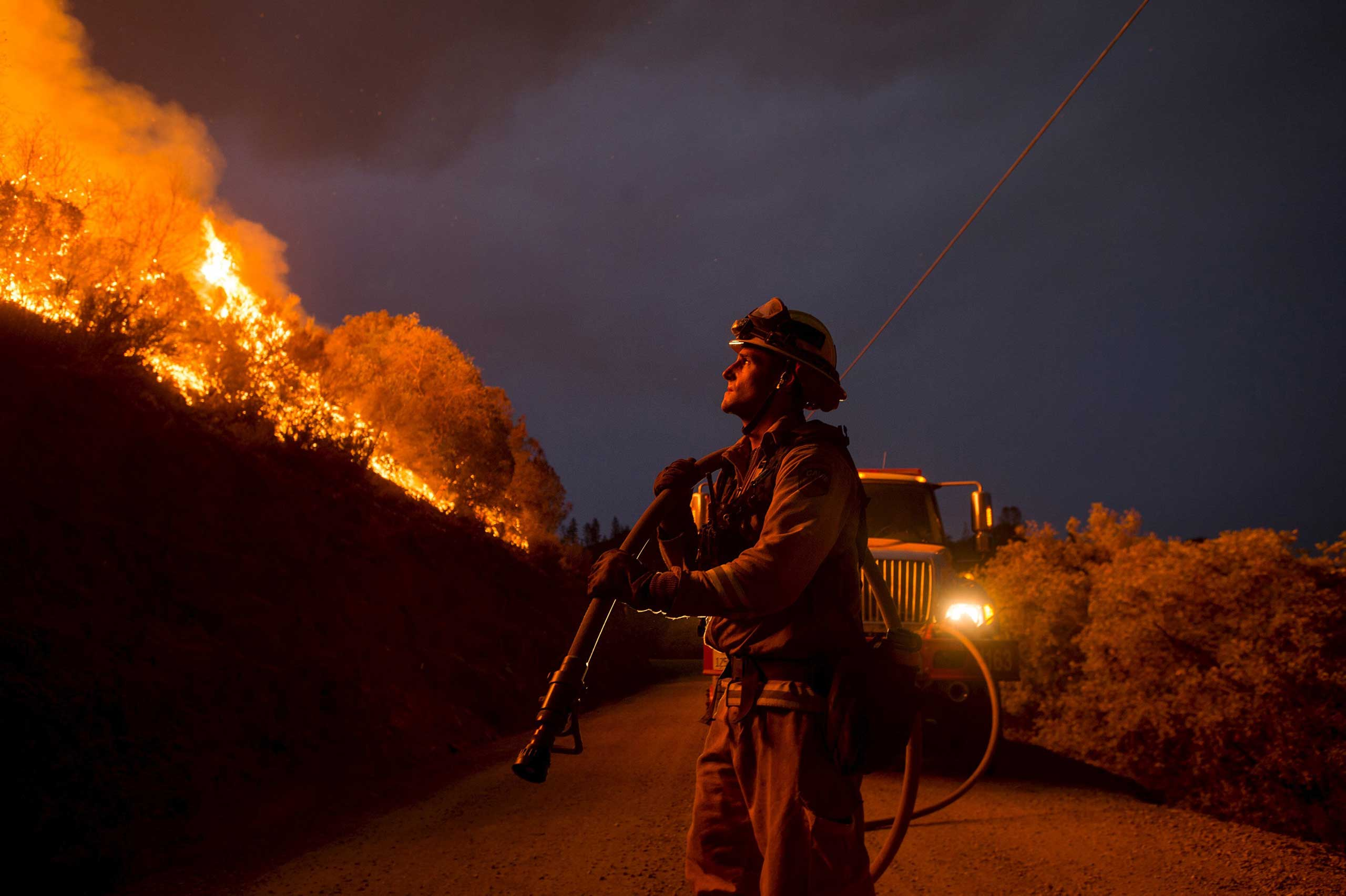 Firefighter Andrew Dodds monitors a backfire while battling the Butte fire near San Andreas, California September 12, 2015.