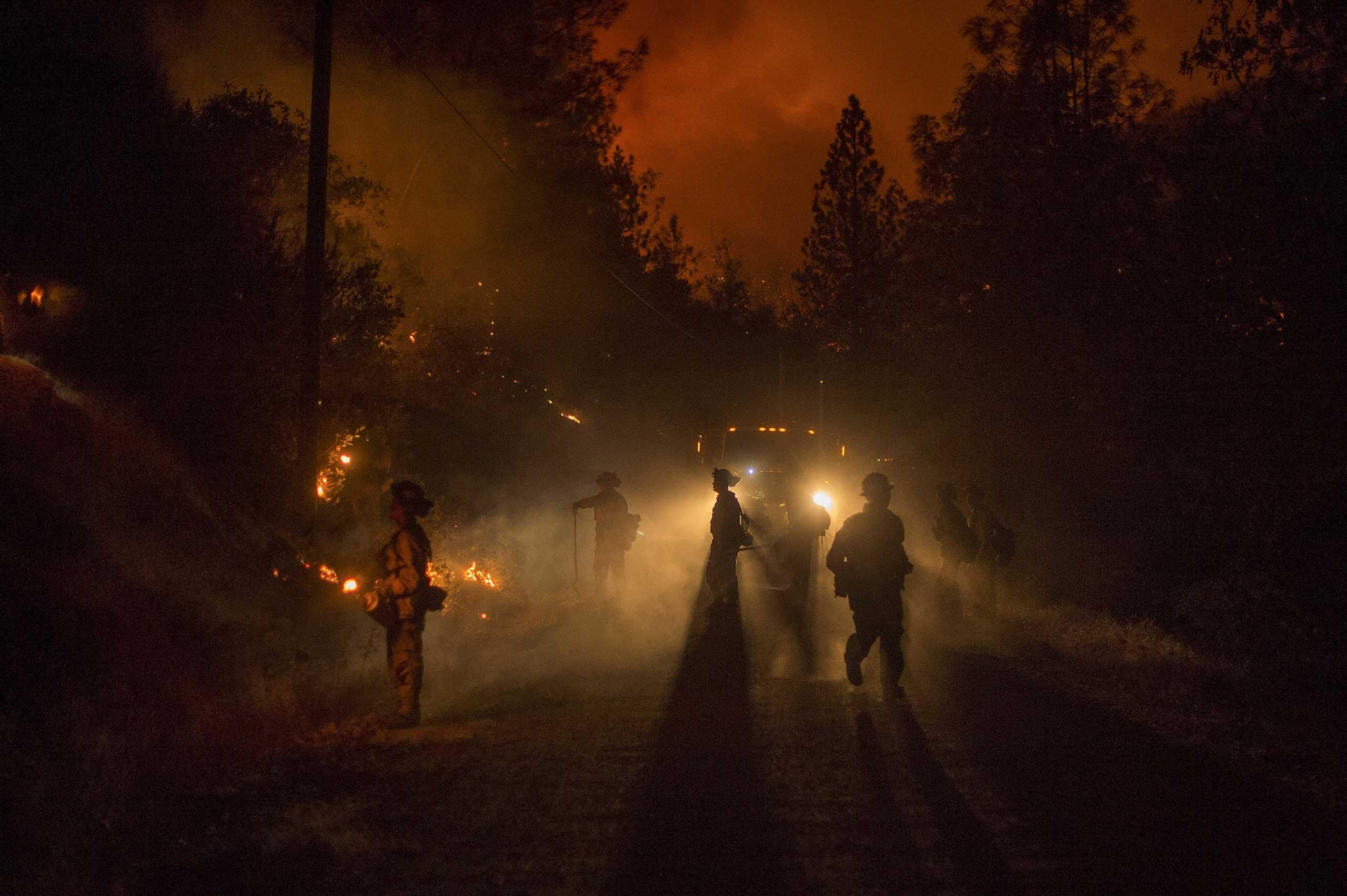 Firefighters light a backfire while battling the Butte fire near San Andreas, California September 12, 2015.
