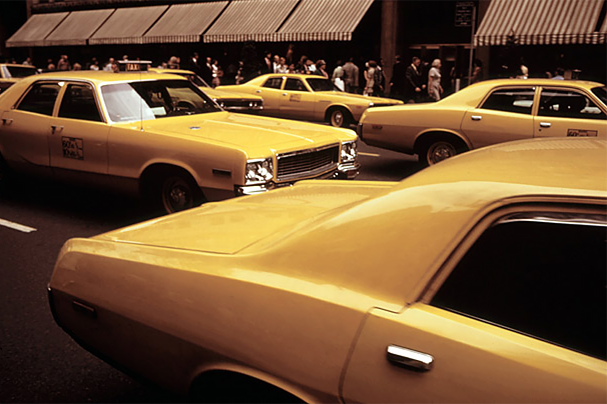 "Taxis drive through the streets of Manhattan near 5th Avenue in New York City, 1972. The vehicles' signature yellow livery didn't become law until 1967, when the city ordered that all licensed ""medallion taxis"" be painted the same color, in order to cut down on unofficial drivers and make the cabs more recognizable"