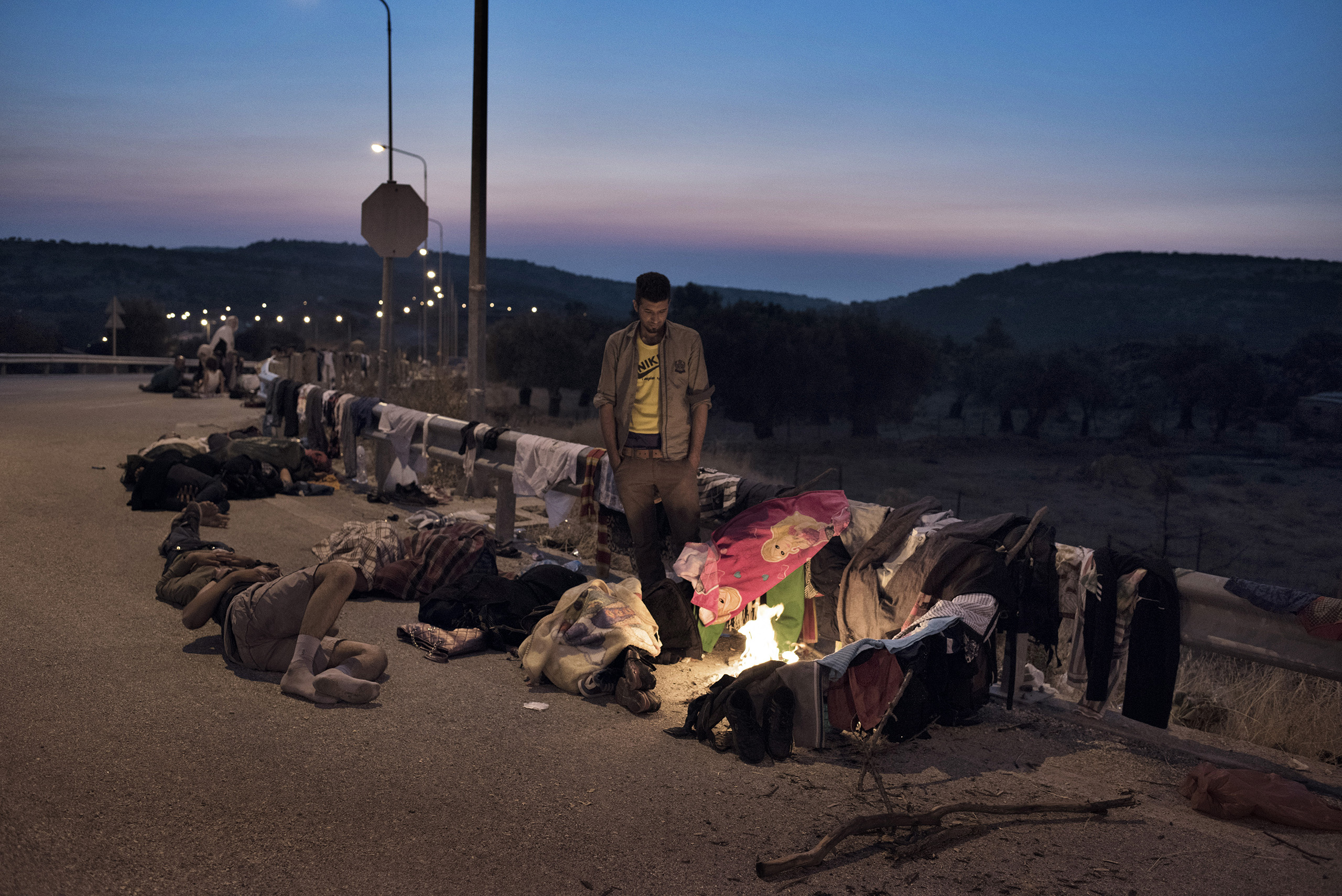 Migrants rest in makeshift camps on the roadside as they make their way on foot across the Greek island of Lesbos, the first piece of European land they reached after crossing in rickety boats from neighboring Turkey.