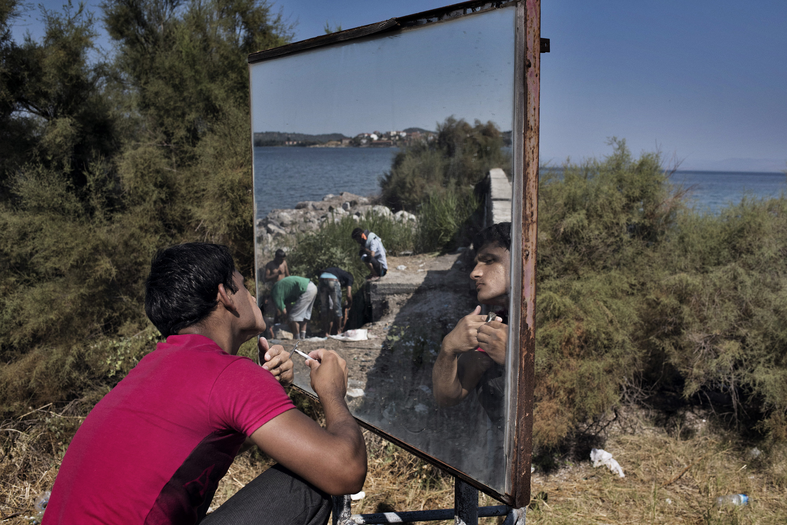 An Afghan migrant shaves with the help of a traffic mirror on the side of a highway on the Greek island of Levos.