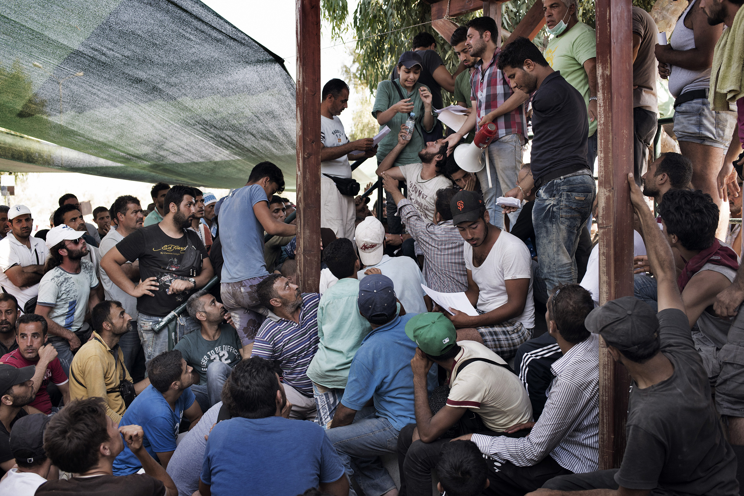 Migrants wait at a camp for asylum seekers on the Greek island of Lesbos to receive registration documents from Greek authorities that will allow them to leave the island on ferries and travel onward toward Western Europe.