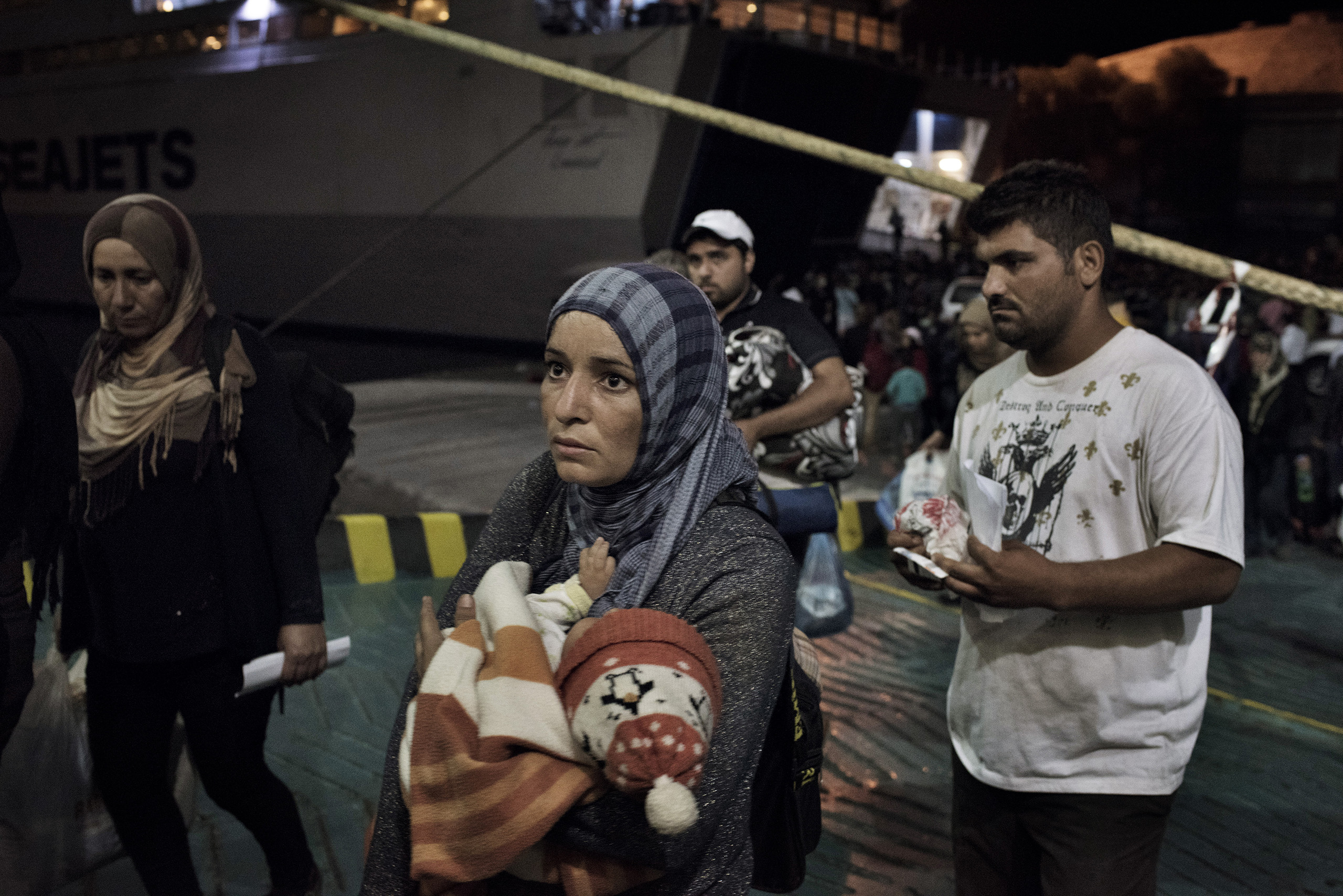 Migrants come aboard a cruise ship that the Greek government chartered to transport them to Athens from the Greek island of Lesbos. The regular ferry service traveling this route was unable to cope with the unprecedented influx of migrants going through Greece to Western Europe from various conflict zones across the Muslim world.