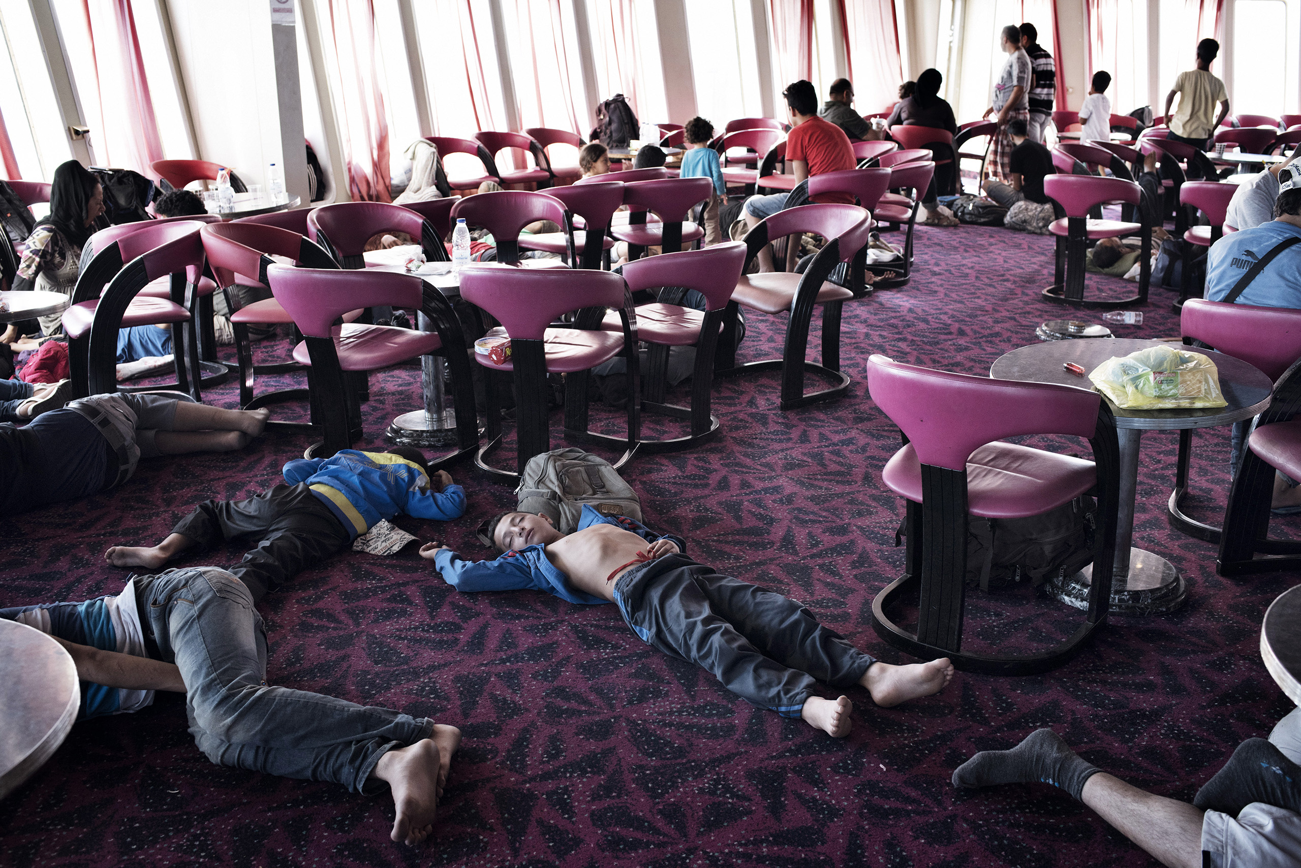 Migrants rest and recharge their phones aboard a cruise ship that the Greek government chartered to transport them to Athens from the Greek island of Lesbos. The regular ferry service traveling this route was unable to cope with the unprecedented influx of migrants going through Greece to Western Europe from various conflict zones across the Muslim world.