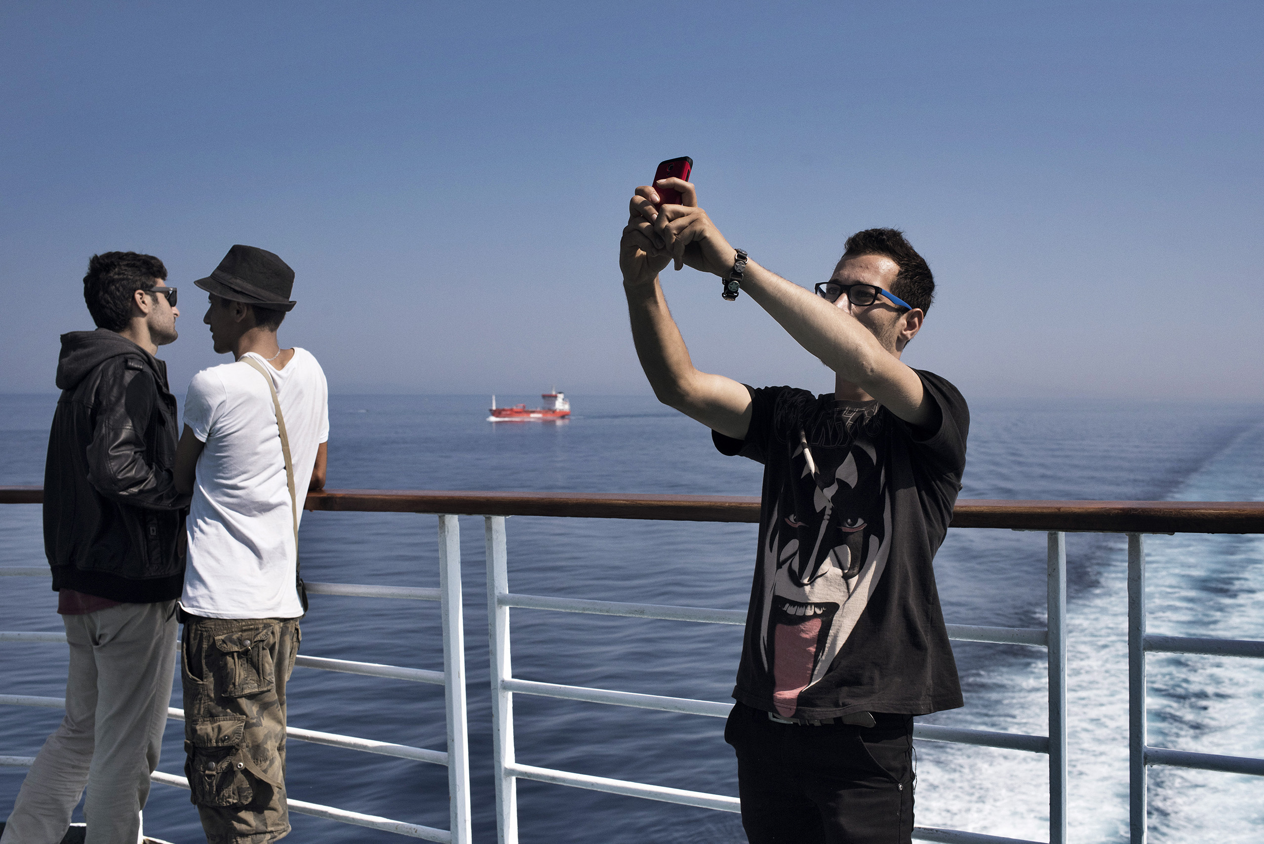 A migrant takes a selfie aboard a cruise ship that the Greek government chartered to transport them to Athens from the Greek island of Lesbos.