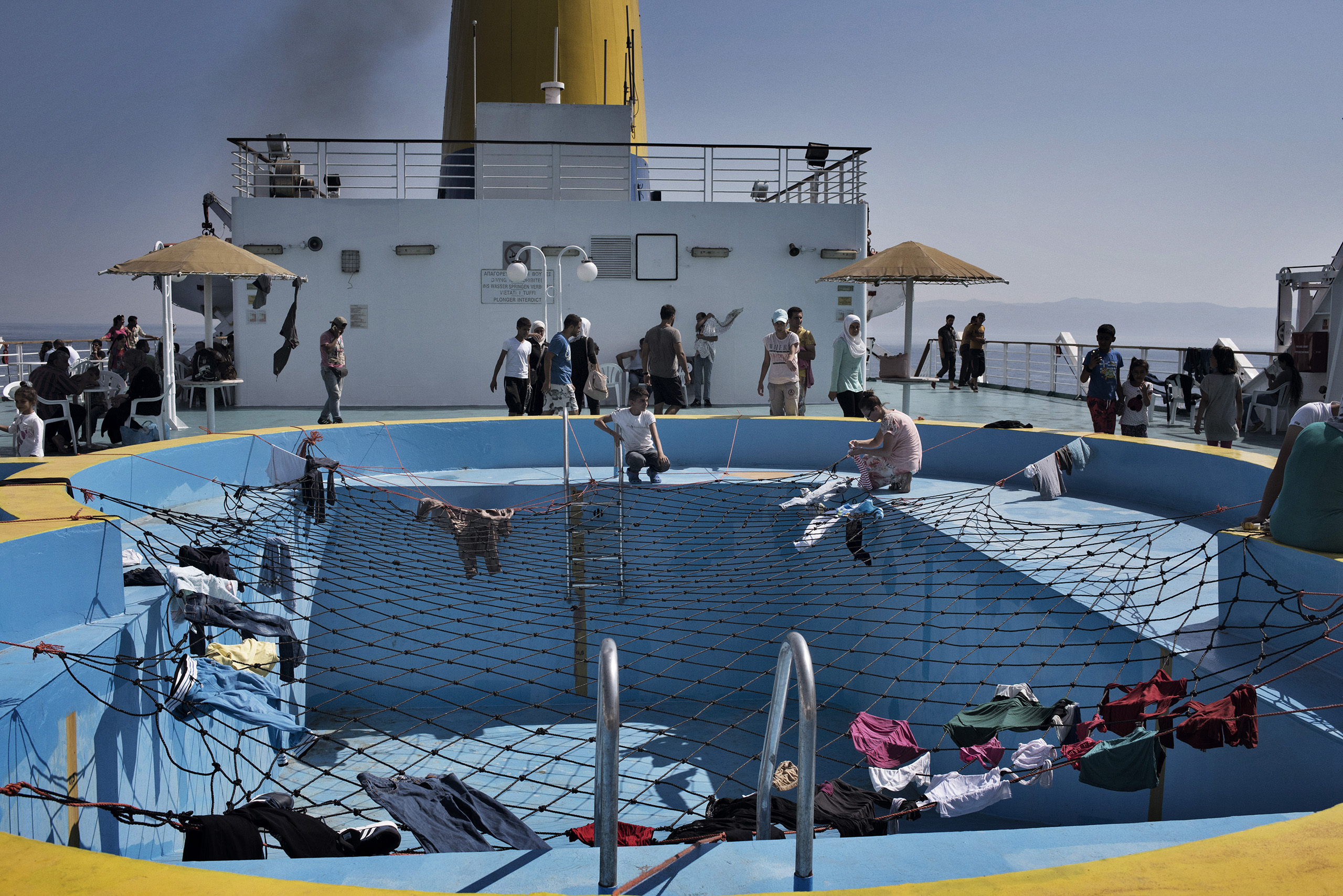 Migrants use the netting over a swimming pool to dry their laundry aboard a cruise ship that the Greek government chartered to transport them to Athens from the Greek island of Lesbos.