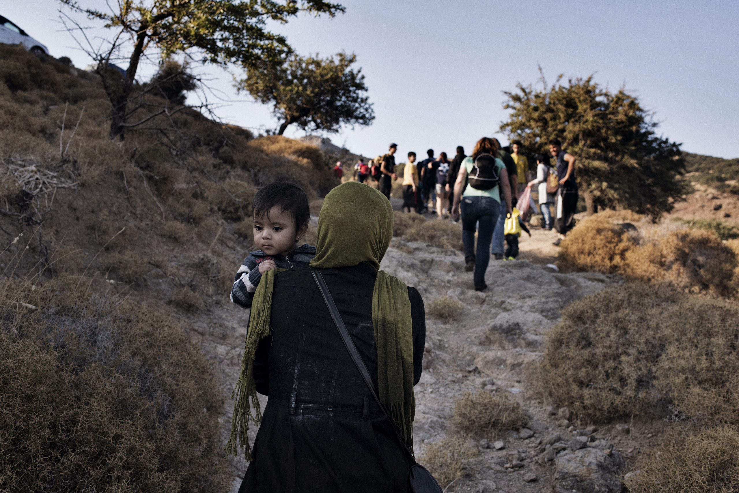 A migrant carries her child up from the beach to a road on the Greek island of Lesbos, the first piece of European land they reached after crossing from Turkey with a few dozen other migrants in an overcrowded motorboat.