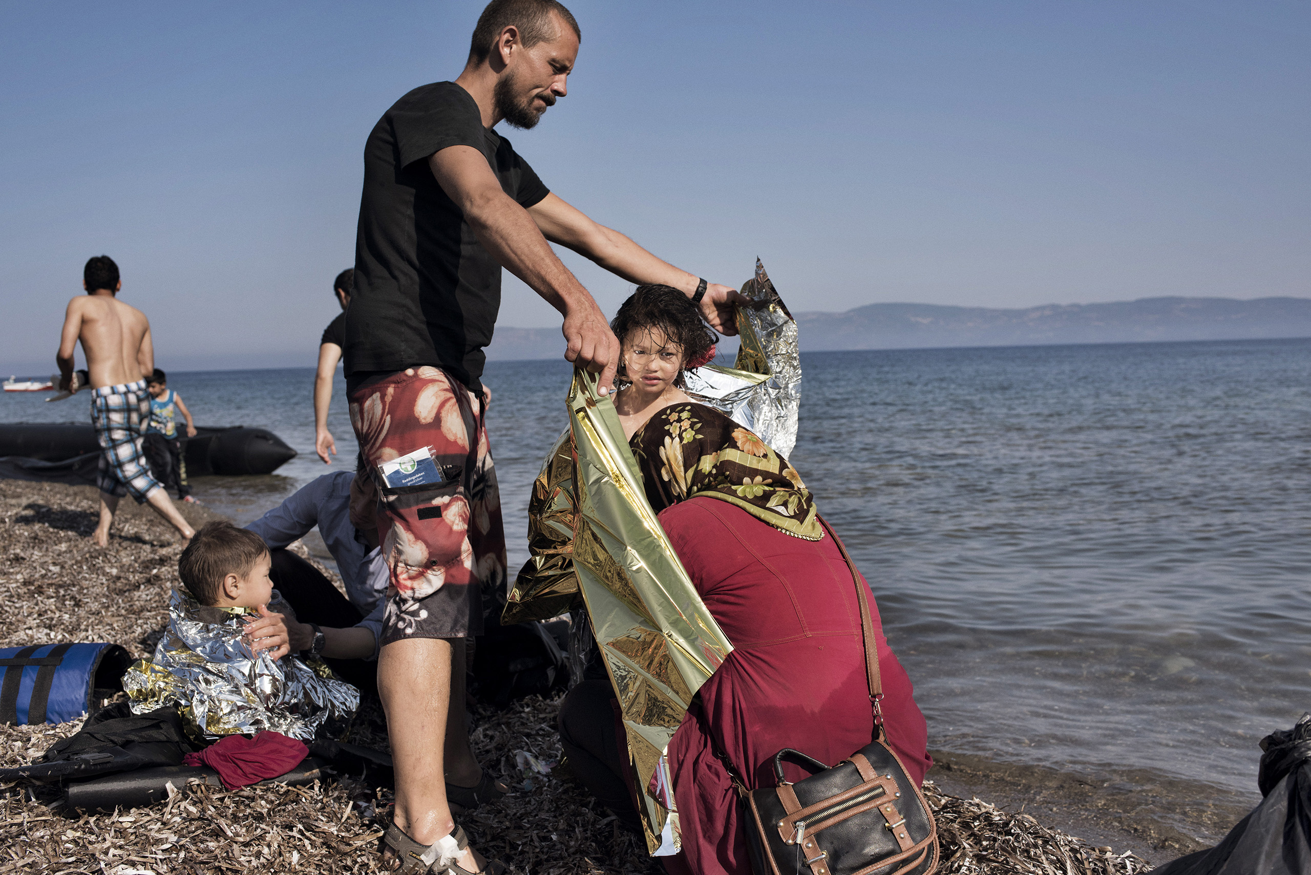 A German volunteer helps a family from Afghanistan that has just come ashore from Turkey on the Greek island of Lesbos, the first piece of European land they reached on their journey to claim asylum in Germany and other wealthy European nations.
