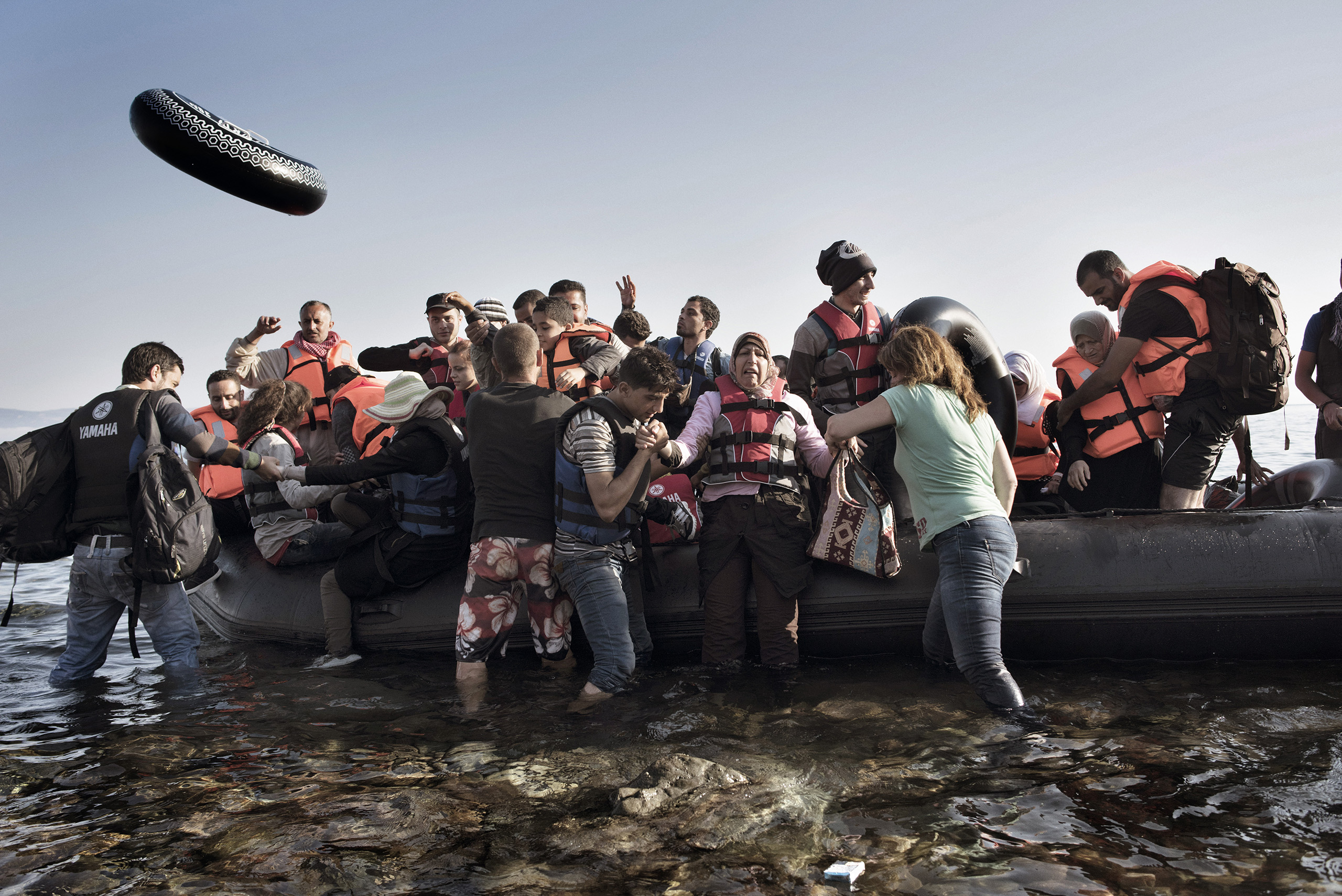 Volunteers rush to welcome a boat full of migrants as it arrives on the Greek island of Lesbos.