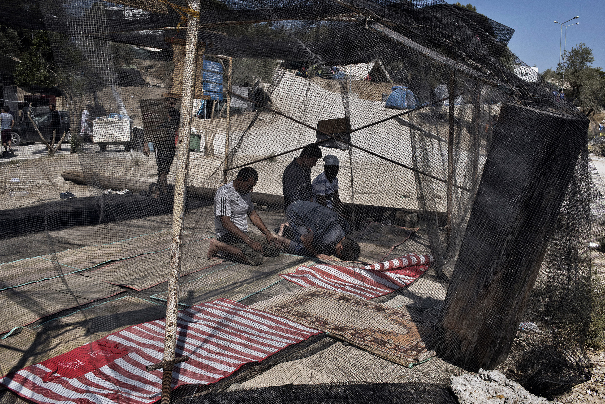 Migrants pray at the makeshift mosque they have built inside a detention and processing camp for asylum seekers on the Greek island of Lesbos.