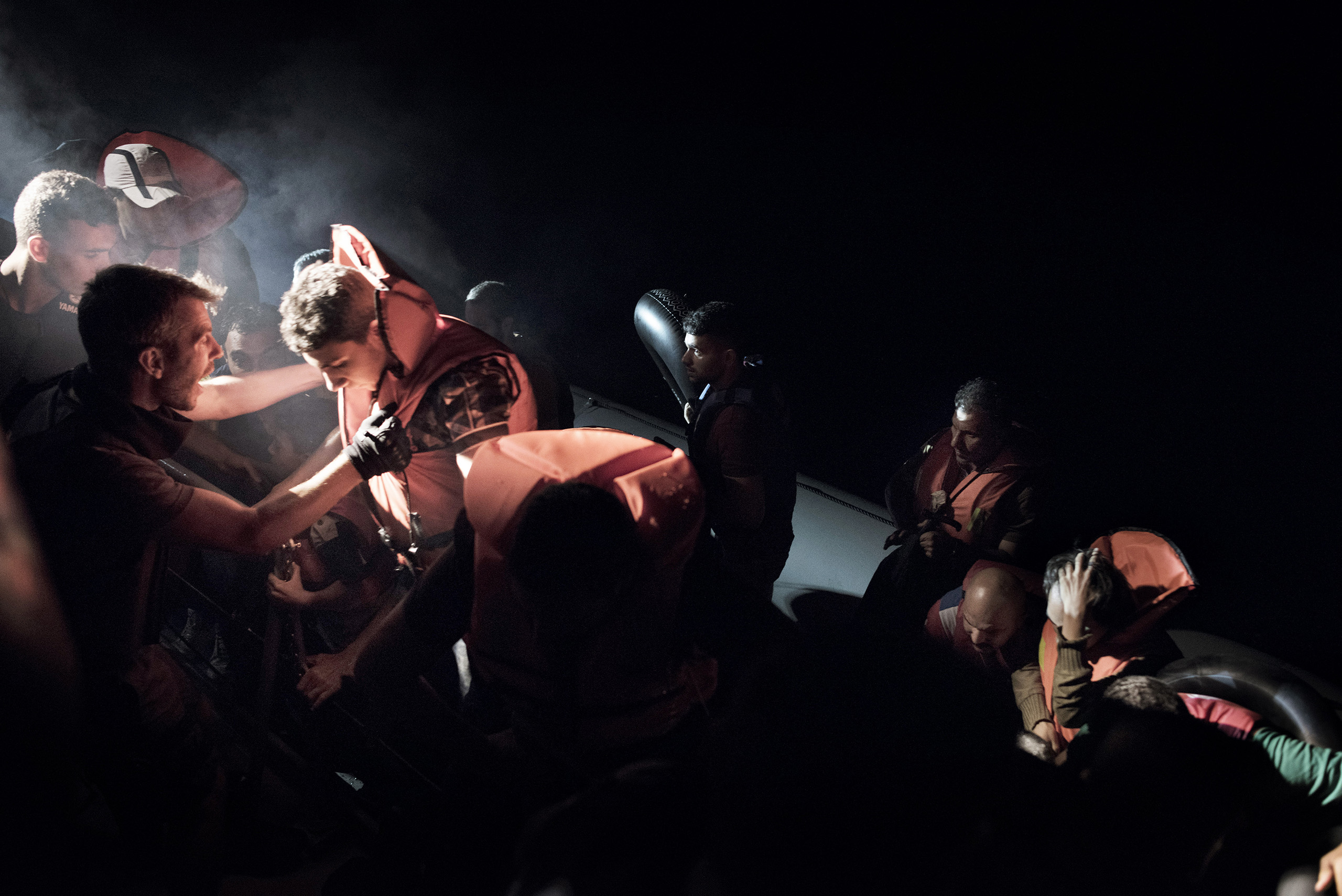 Syrian migrants scramble aboard a Greek coast guard vessel from the rubber motorboat they were using to cross from Turkey to the Greek islands. The coast guards have orders to rescue any migrant boats they find during night patrols of the Aegean Sea and bring them to Greece for processing and registration. Sept. 7, 2015.
