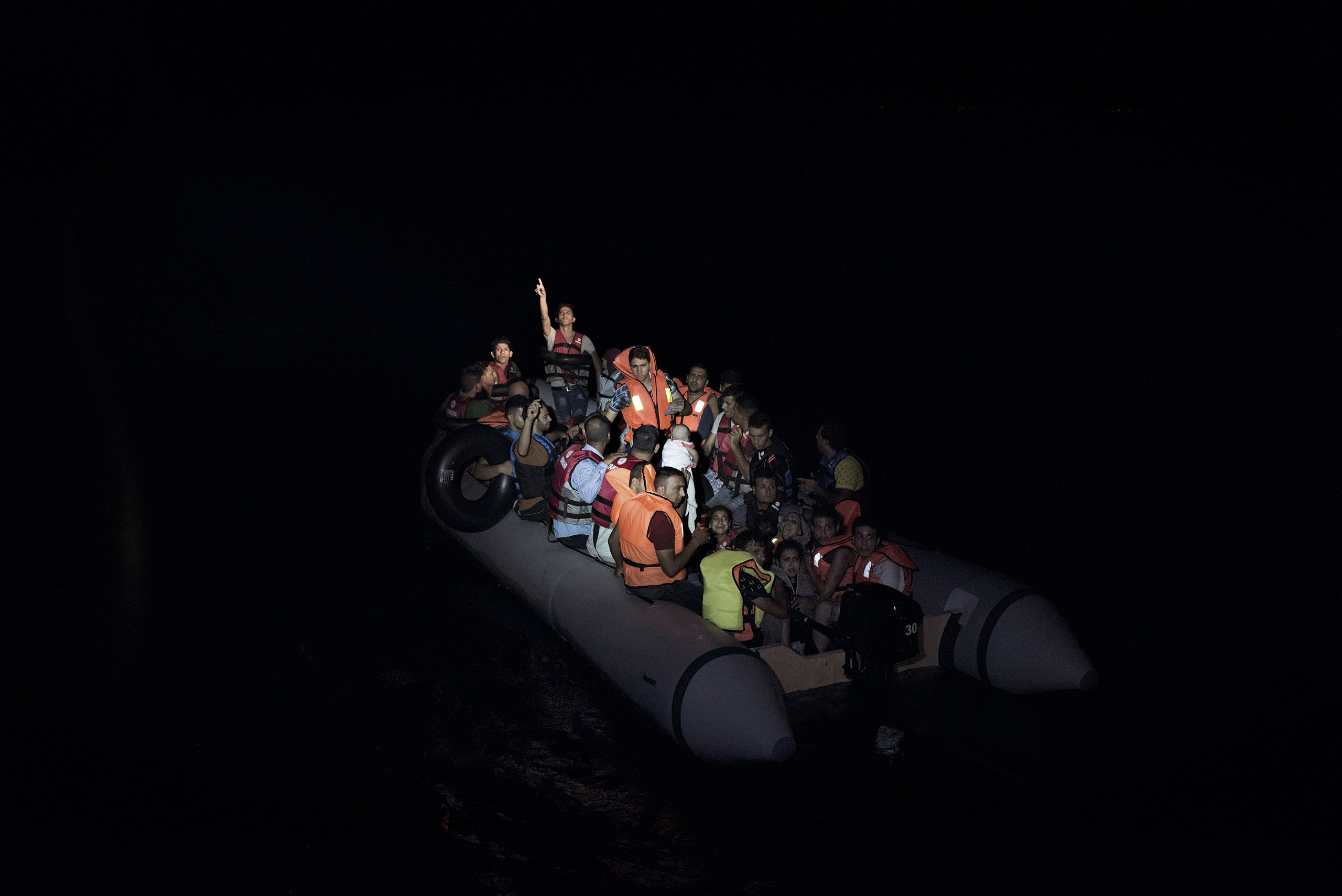 A boat full of migrants is illuminated by the flash lights of Greek coast guards who have come to rescue them from the waters near the Greek-Turkish border. Sept. 7, 2015.