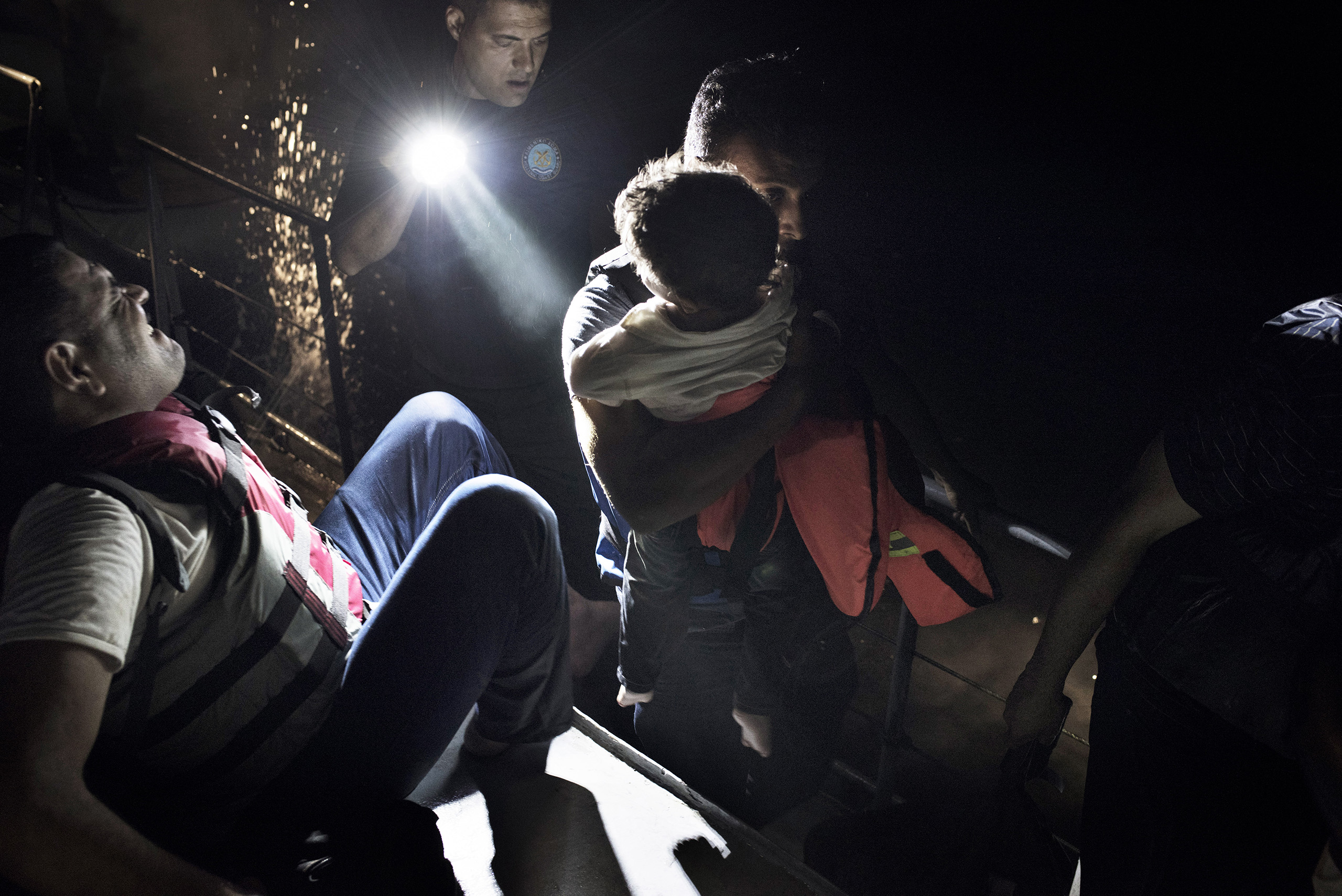 A Greek coast guard lights the way for a group of Syrian migrants as they move to the front of a Greek coastal patrol vessel after being rescued from the waters near the border between Greece and Turkey. Sept. 7, 2015.