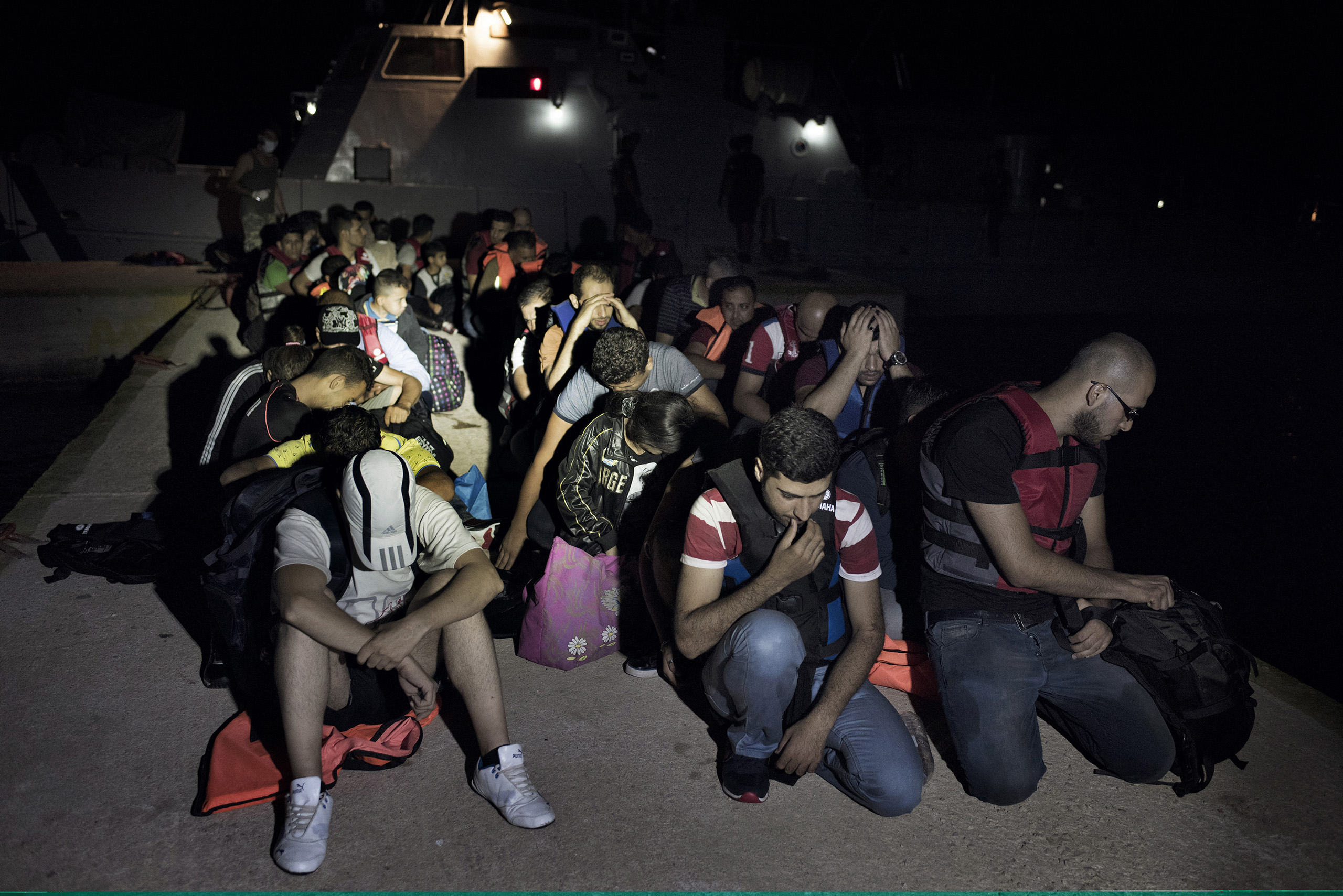 Syrian migrants huddle on the pier of a Greek naval outpost on the island of Farmakonisi after Greek coast guards rescued them from the waters near the border between Greece and Turkey. Sept. 7, 2015.