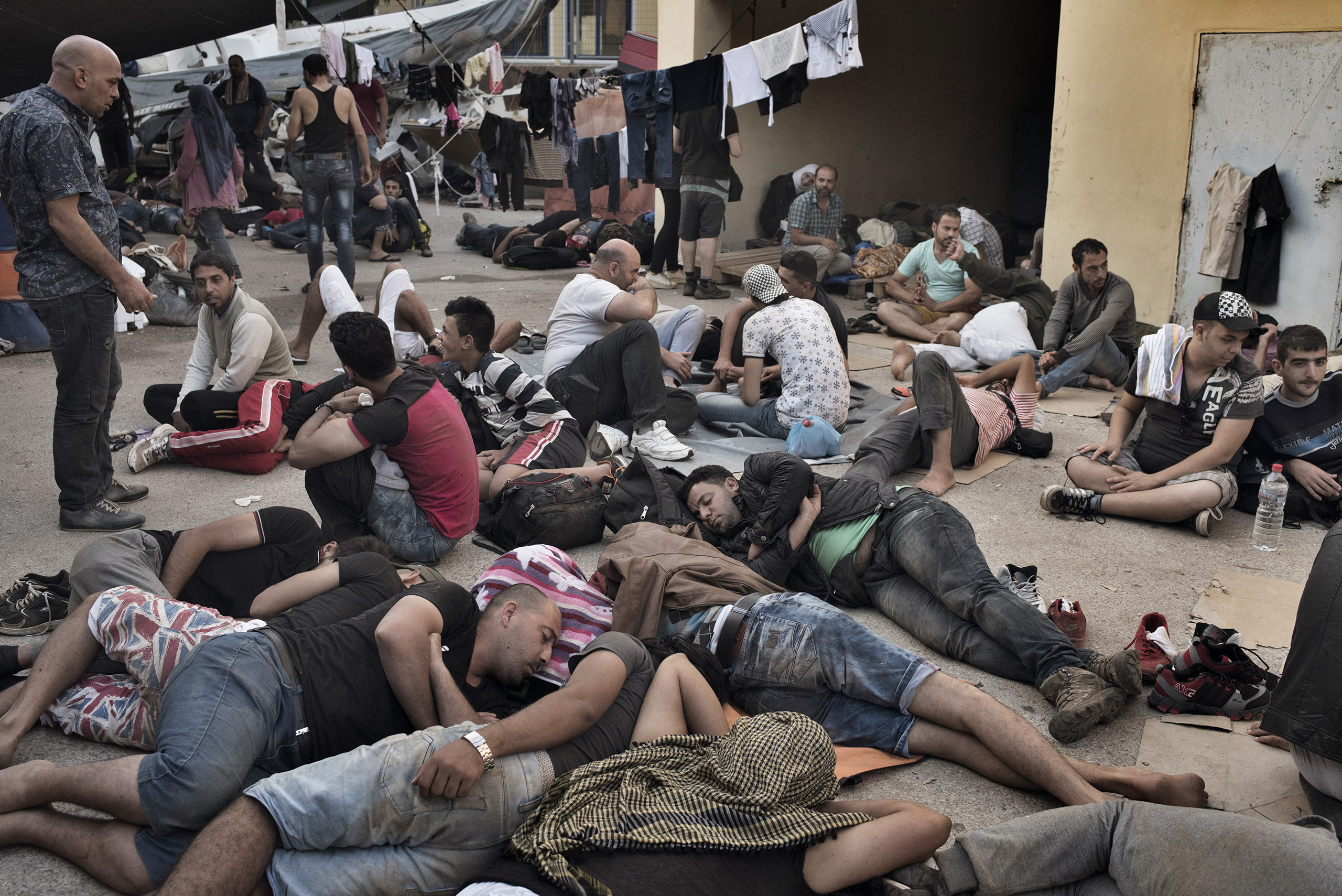 A camp full of migrants awakens in the courtyard of the Greek coast guard's station on the island of Leros, Greece, where they are waiting for the documents they will need to travel onward from to Western Europe. Sept. 5, 2015.