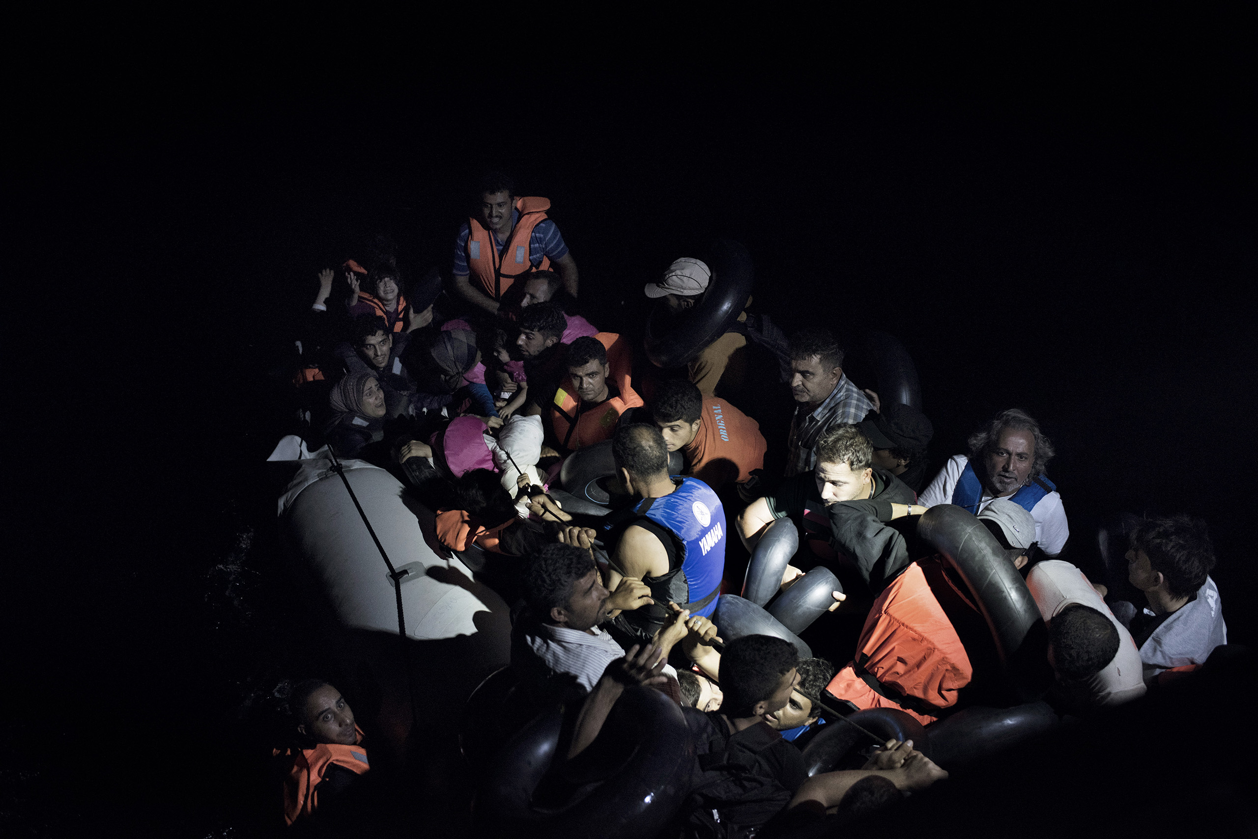 A boat full of migrants is illuminated by the flashlights of Greek coast guards who have come to rescue them from the waters near the Greek-Turkish border. Sept. 6, 2015.