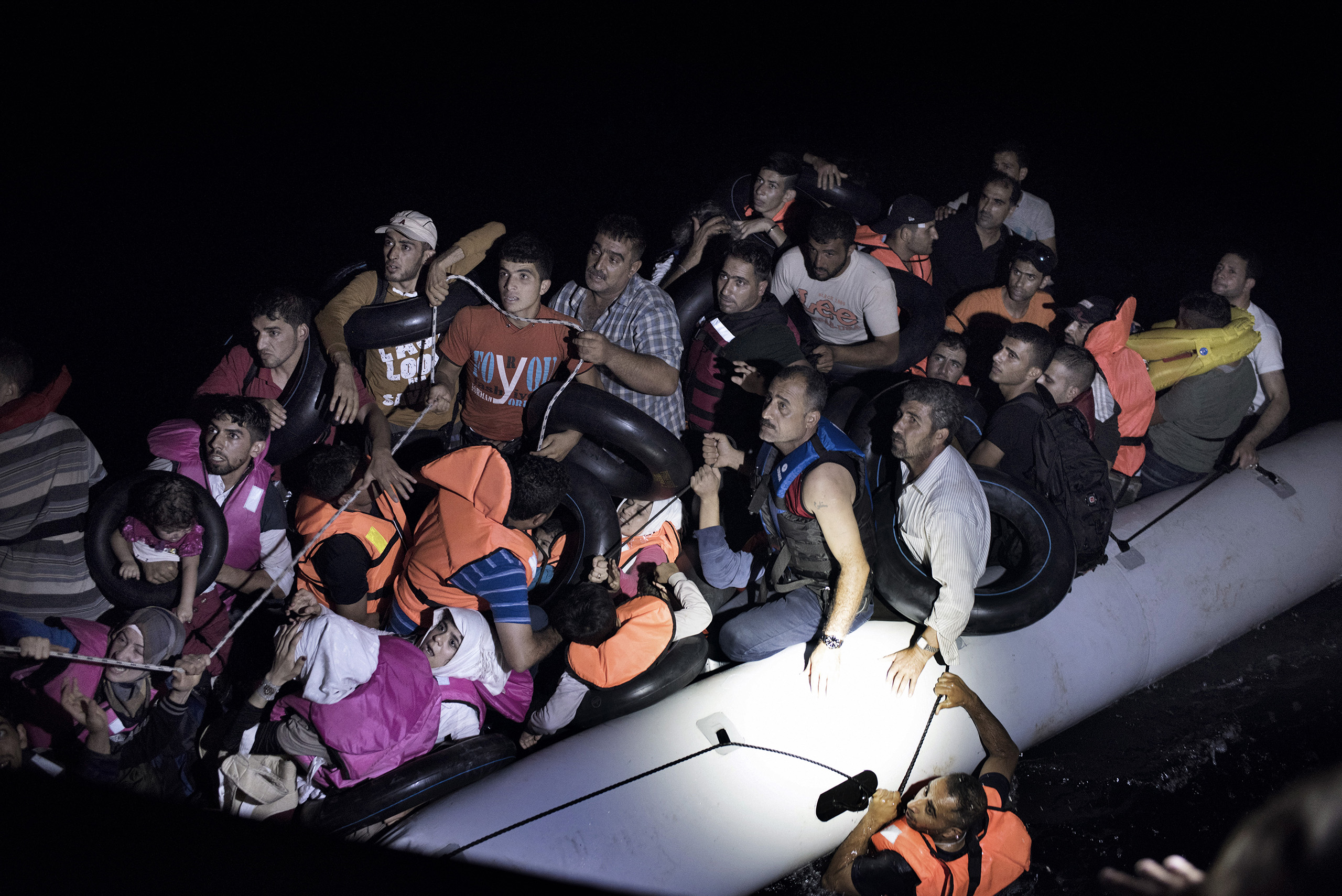A migrant scrambles to climb back aboard a rubber dinghy full of his fellow Syrians as they try to cross from Turkey to the Greek islands on their way to claim asylum in the European Union. Sept. 6, 2015.