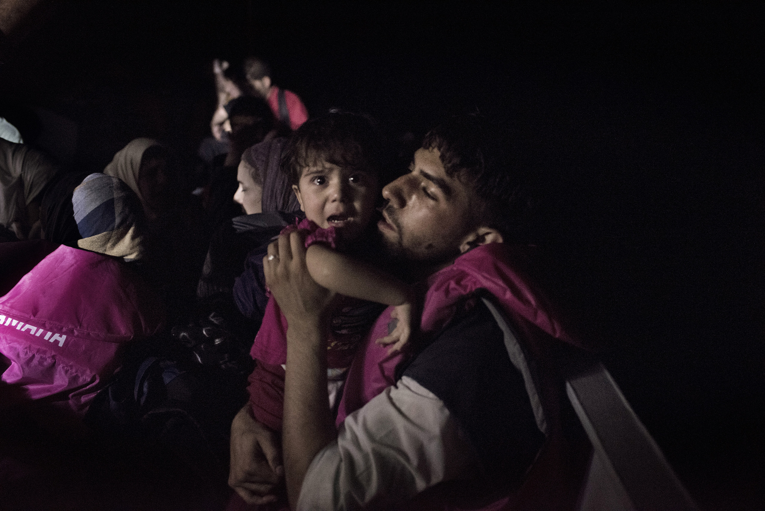 A Syrian migrant comforts his child aboard a Greek coast guard vessel that has just rescued them from an overcrowded motorboat in the waters near the Greek-Turkish border. Sept. 6, 2015.