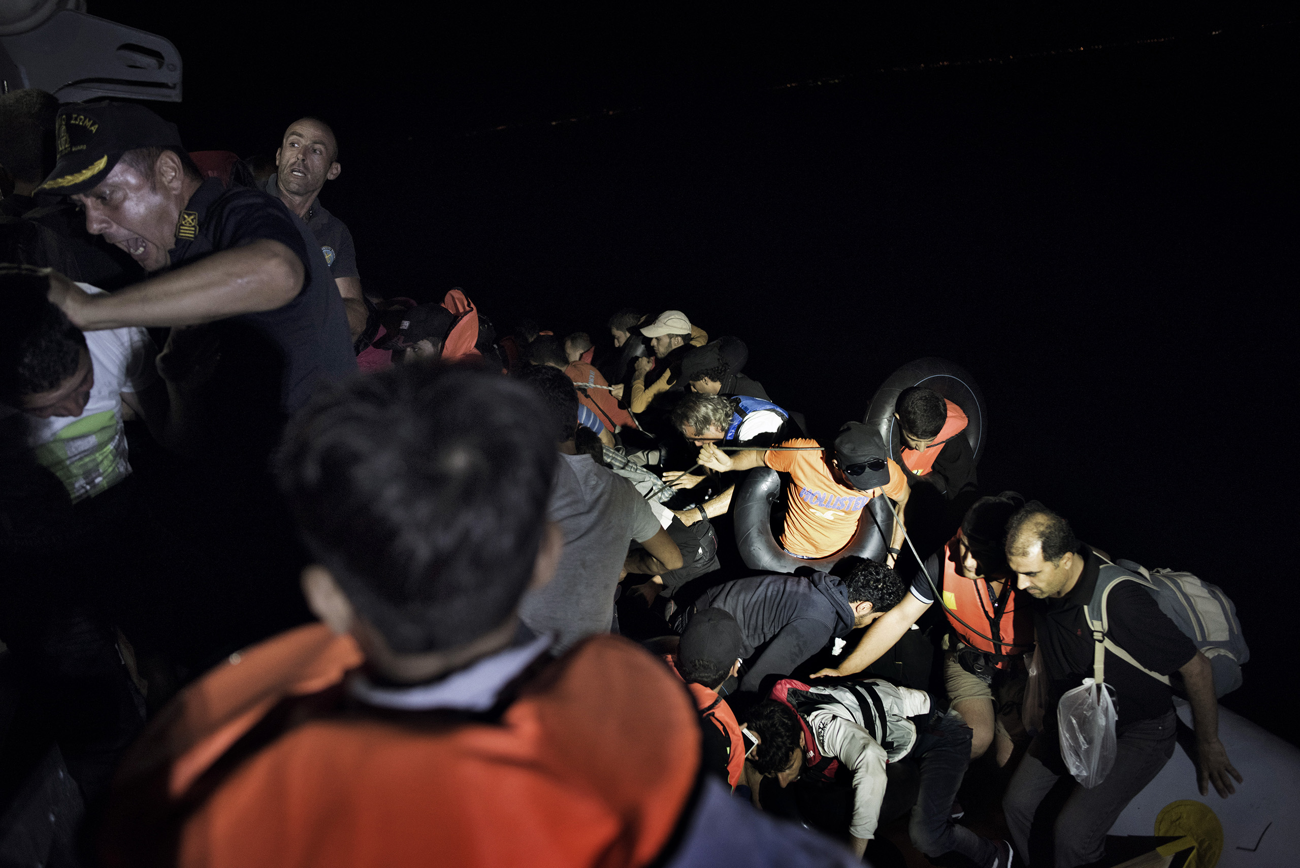 Syrian migrants scramble aboard a Greek coast guard vessel from the rubber motorboat they were using to cross from Turkey to the Greek islands. The coast guards have orders to rescue any migrant boats they find during night patrols of the Aegean Sea and bring them to Greece for processing and registration. Sept. 6, 2015.