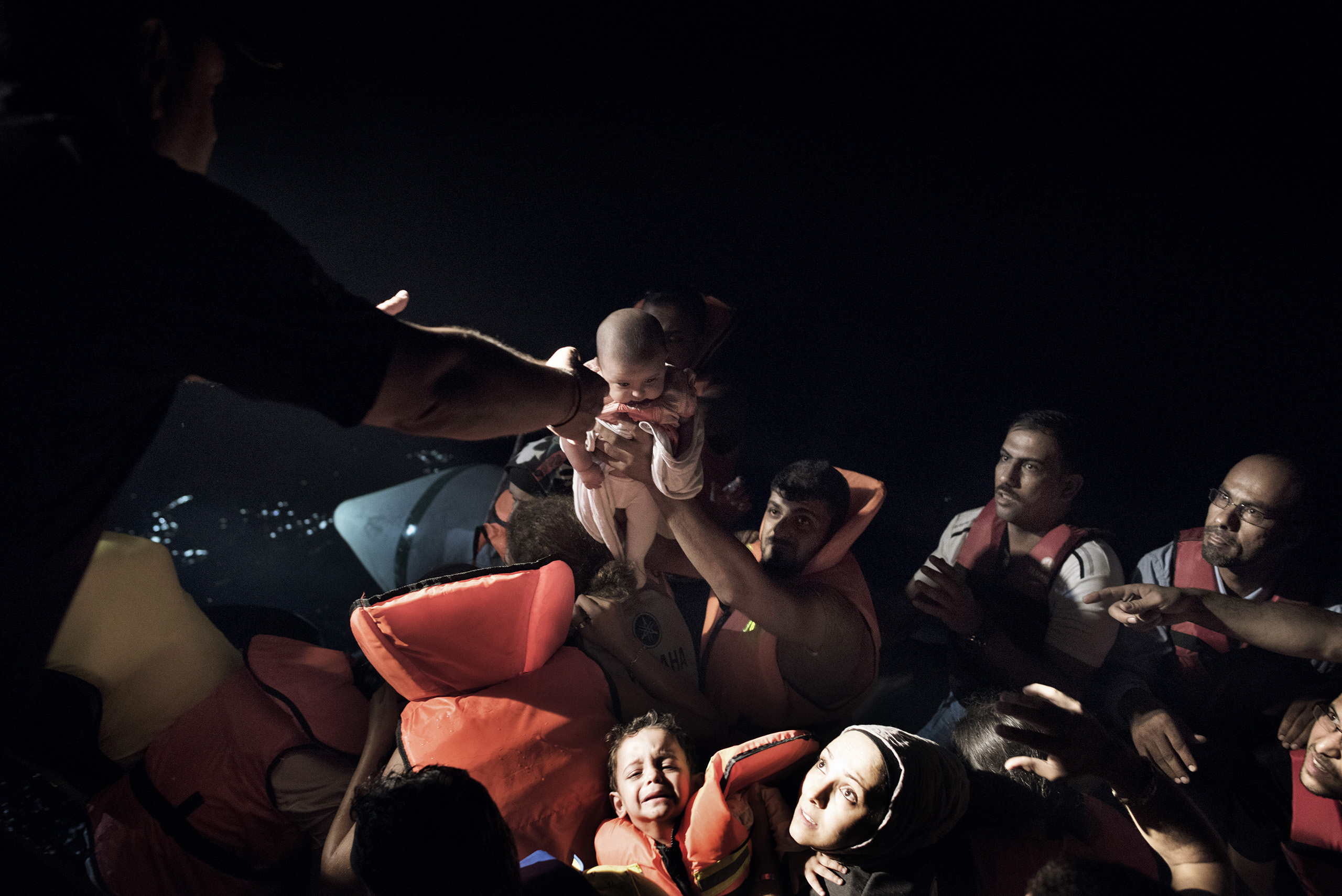 A Syrian migrant aboard a flimsy rubber motorboat hands his one-month-old baby to Greek coast guards, who have arrived to rescue the boat full of migrants from dangerous waters near the border between Greece and Turkey.  Sept. 7, 2015.