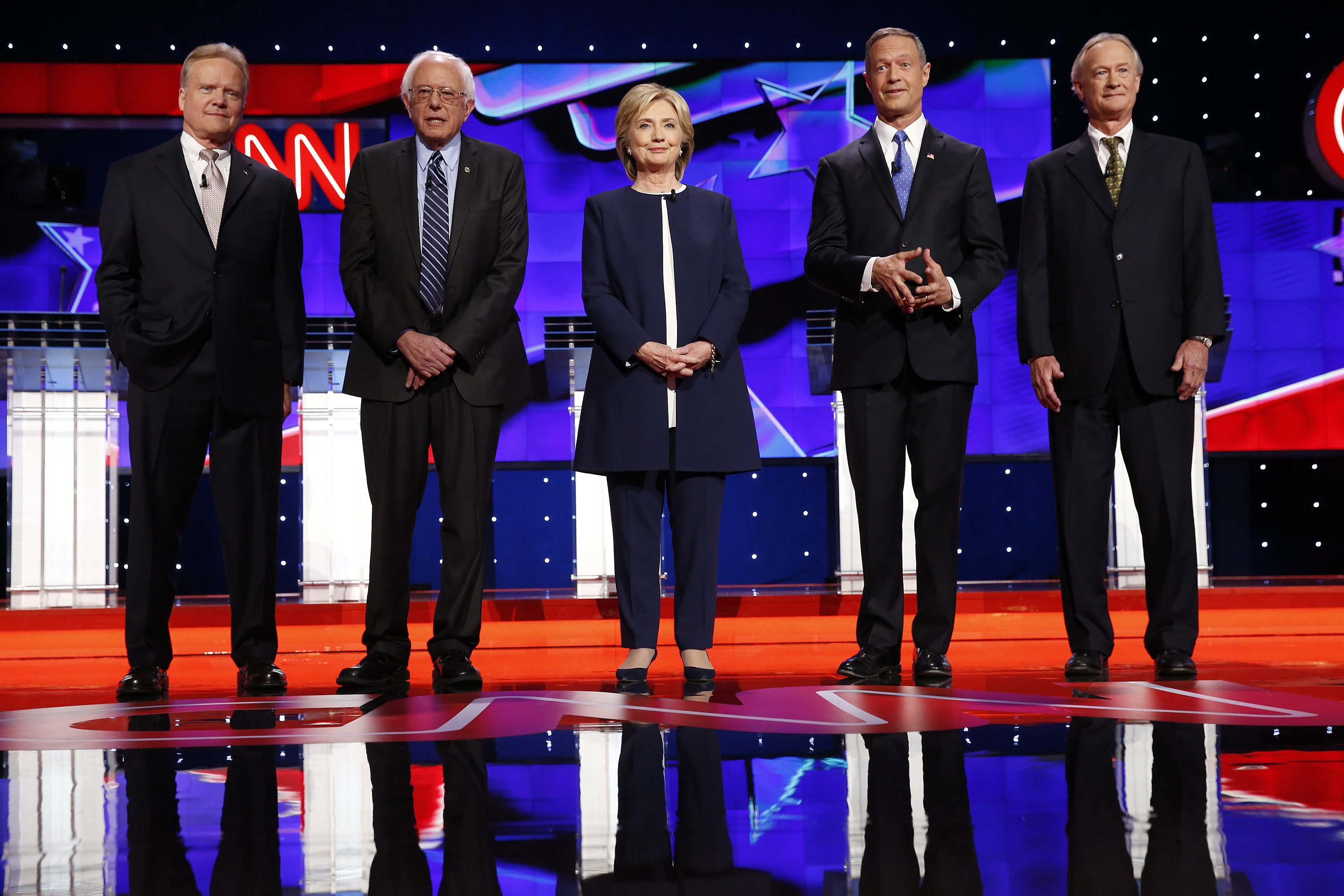 (L-R) Former Virginia Senator Jim Webb,  Vermont Senator Bernie Sanders, former US Secretary of State Hillary Clinton, former Maryland Governor Martin O'Malley and former Rhode Island Governor Lincoln Chafee during the national anthem at the start of the US Democratic Presidential  candidates debate at Wynn Las Vegas in Las Vegas, Nevada, on Oct. 13 2015.