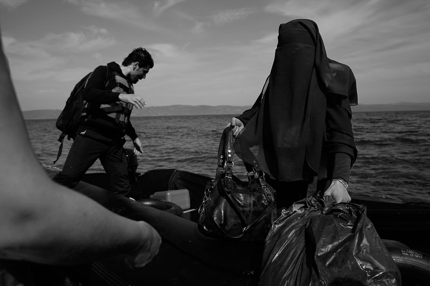 A veiled Muslim woman carries both a handbag and garbage bag holding her possessions while getting off an inflatable boat after arriving on the beach in Lesbos, Greece, Sept. 26, 2015.