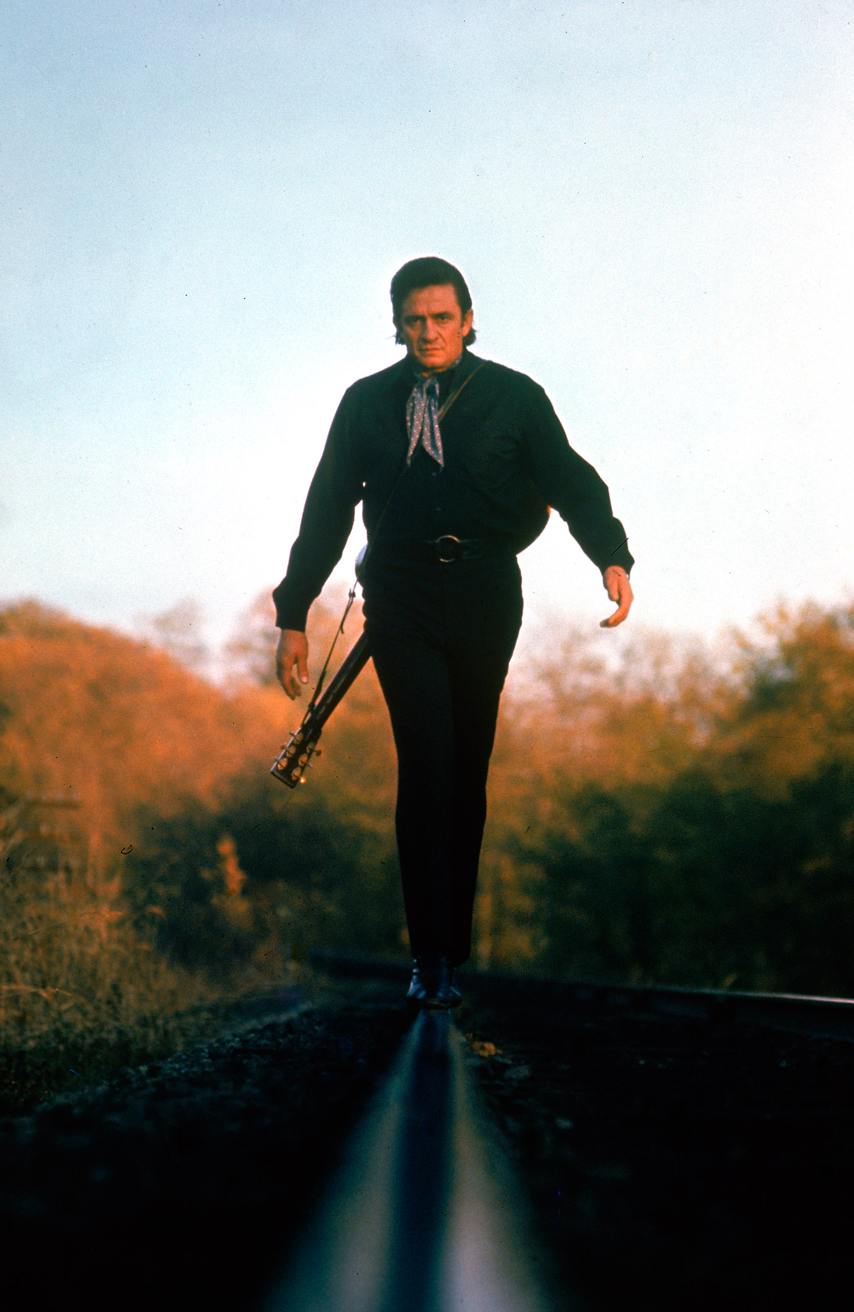 """Walk the line like """"Man in Black"""" Johnny Cash (pictured in 1969), with a guitar slung over the shoulder, a patterned ascot, and head-to-toe black."""