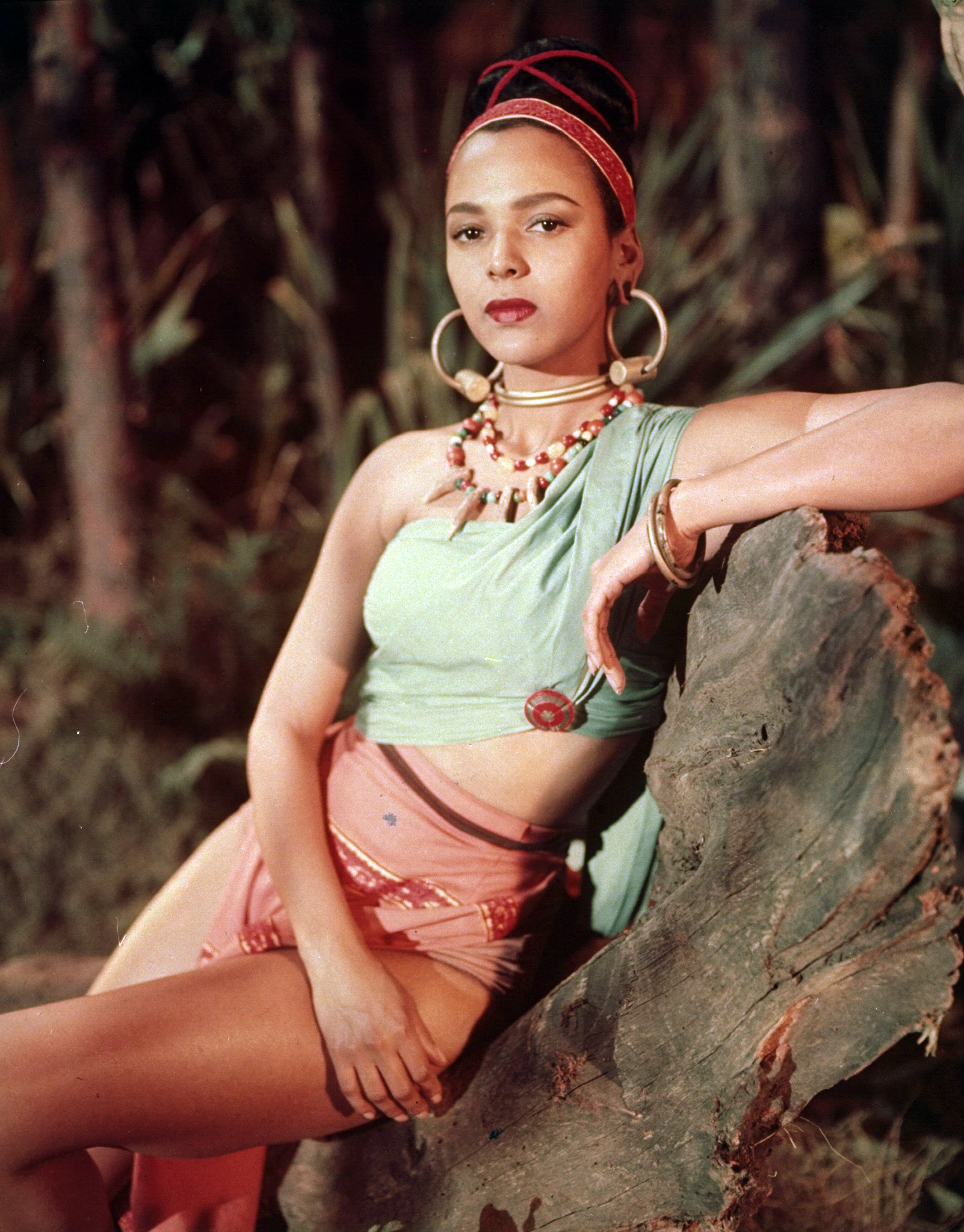 """Dress as Dorothy Dandridge as Melmendi in """"Tarzan's Peril"""" (1951) with a colorful one-shouldered crop top, revealing skirt, hoop earrings and large beaded necklace."""