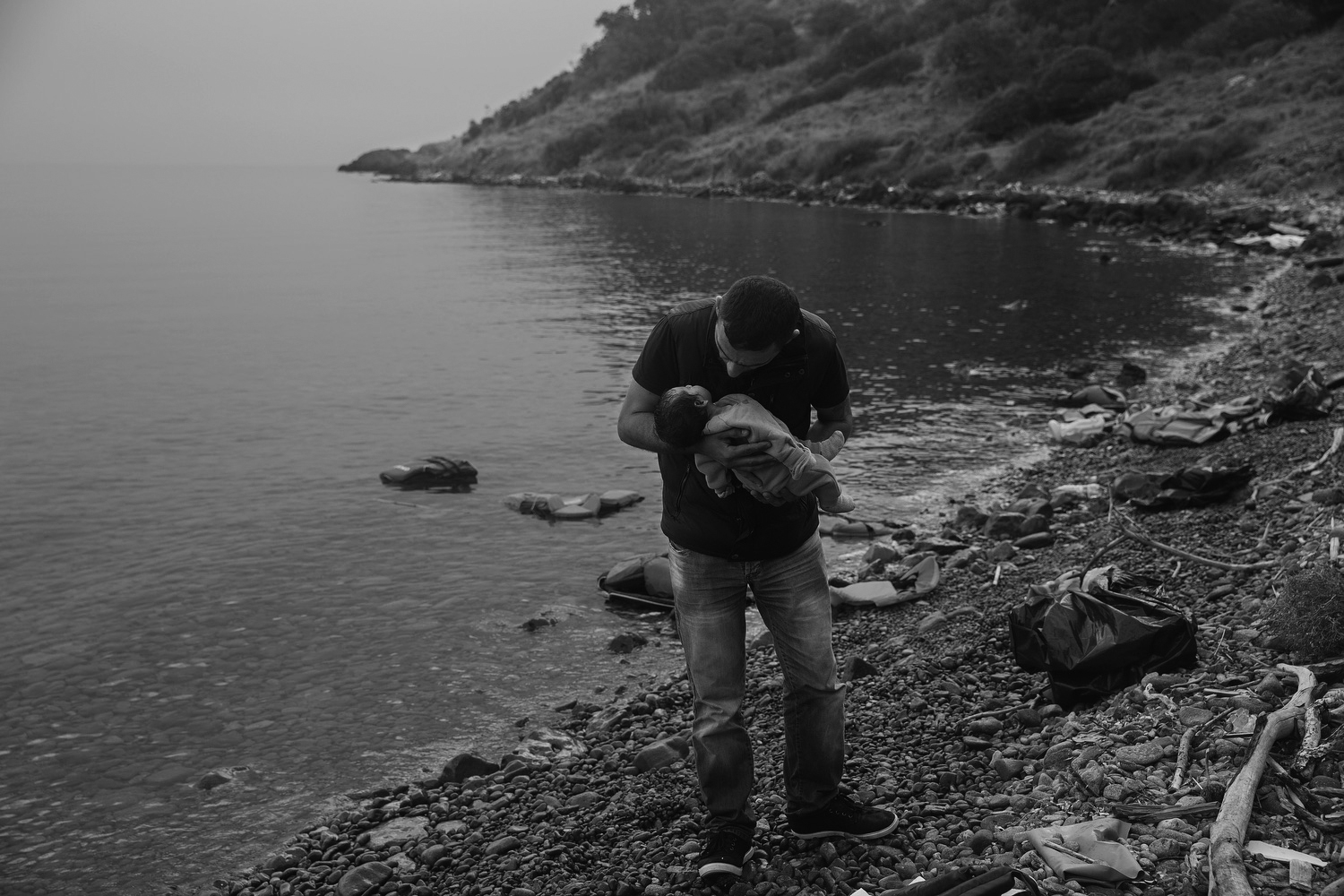 A man hold his baby on the beach in Lesbos, Greece after making the journey with his wife from Turkey, Sept. 28, 2015.