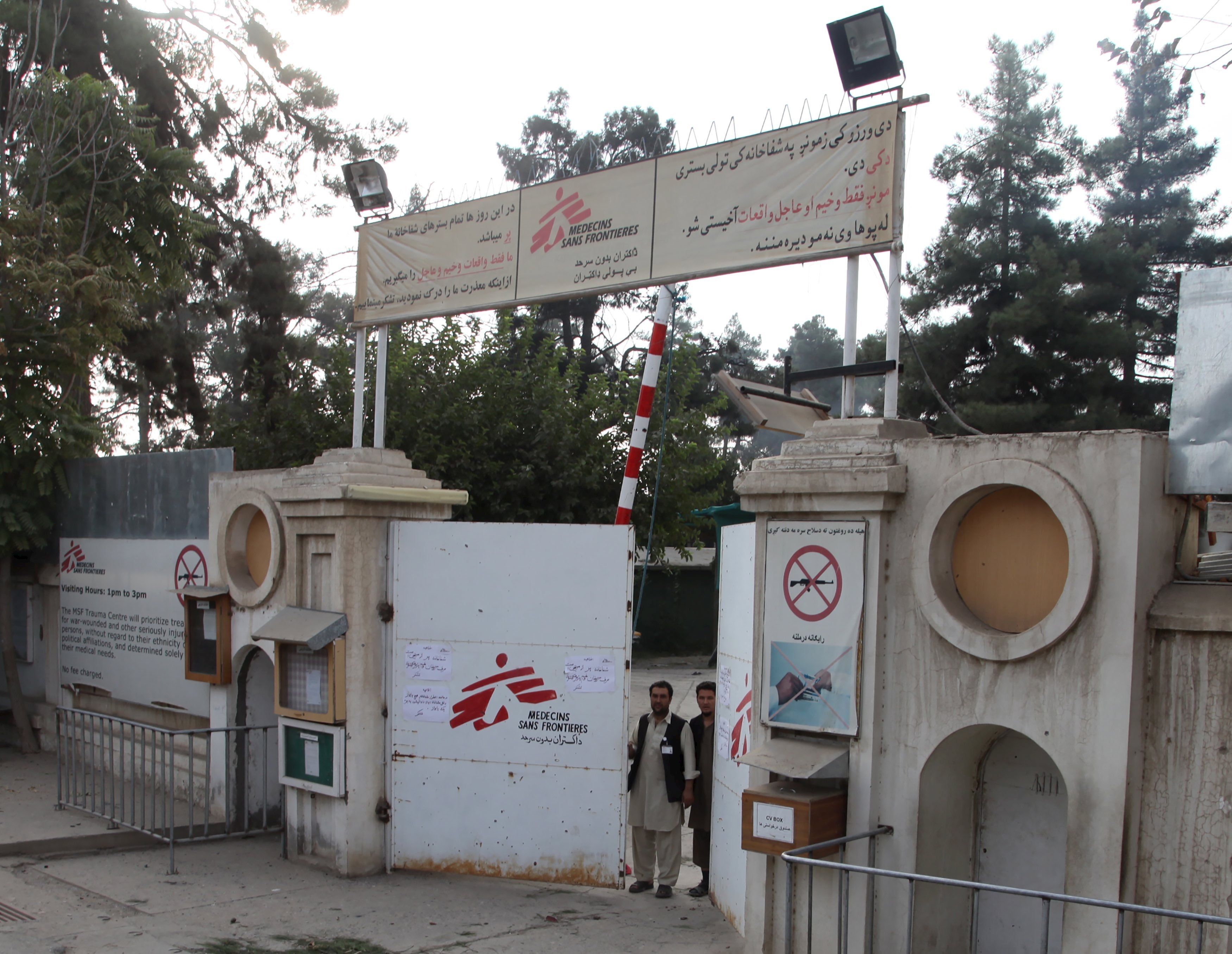 Afghan guards stand at the gate of Medecins Sans Frontieres (MSF) hospital after an air strike in the city of Kunduz, Afghanistan on Oct. 3, 2015.