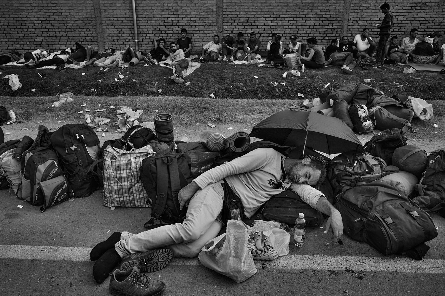 A man sleeps as he waits for a bus that will take him further into Croatia. Refugees line up their bags to save their place in the long lines for the few buses dispatched each day, Sept. 18, 2015.