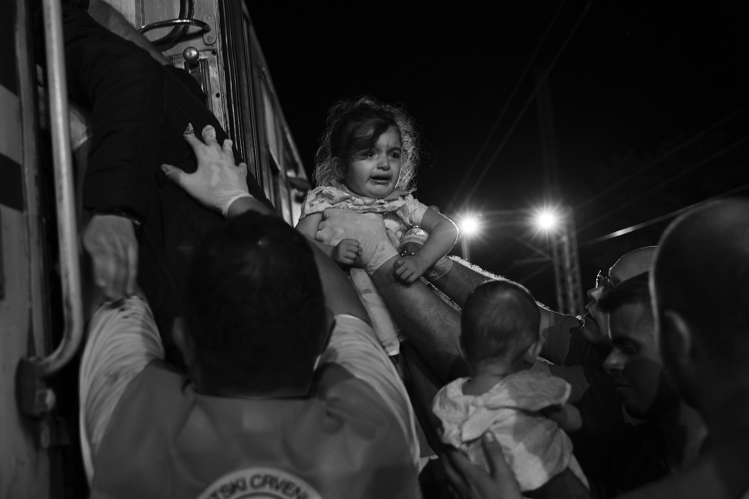 Local NGO workers carry a young girl onto a train in Tovarnik dispatched to transport refugees further into Croatia. 17, 2015.