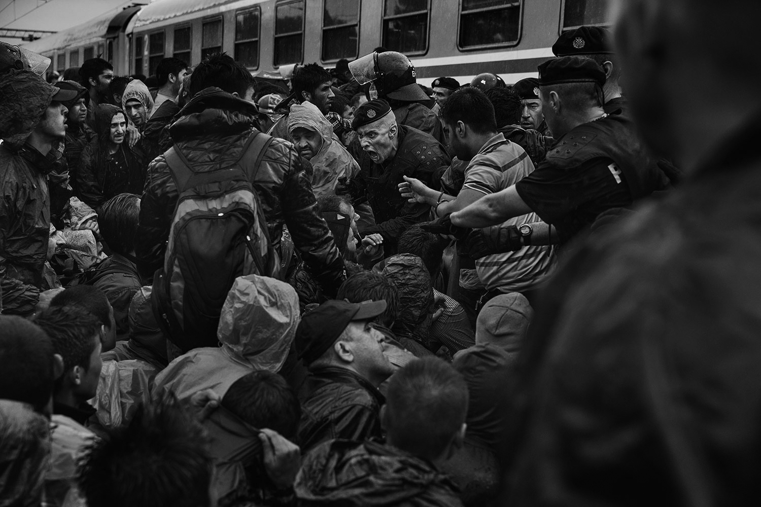 A police officer screams at refugees as they attempt to board a train in Tovarnik, Croatia, Sept. 17, 2015.
