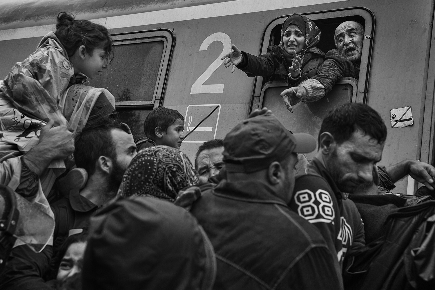 Refugees plead with police officers to let members of their families board the train in Tovarnik, Croatia, Sept. 17, 2015.